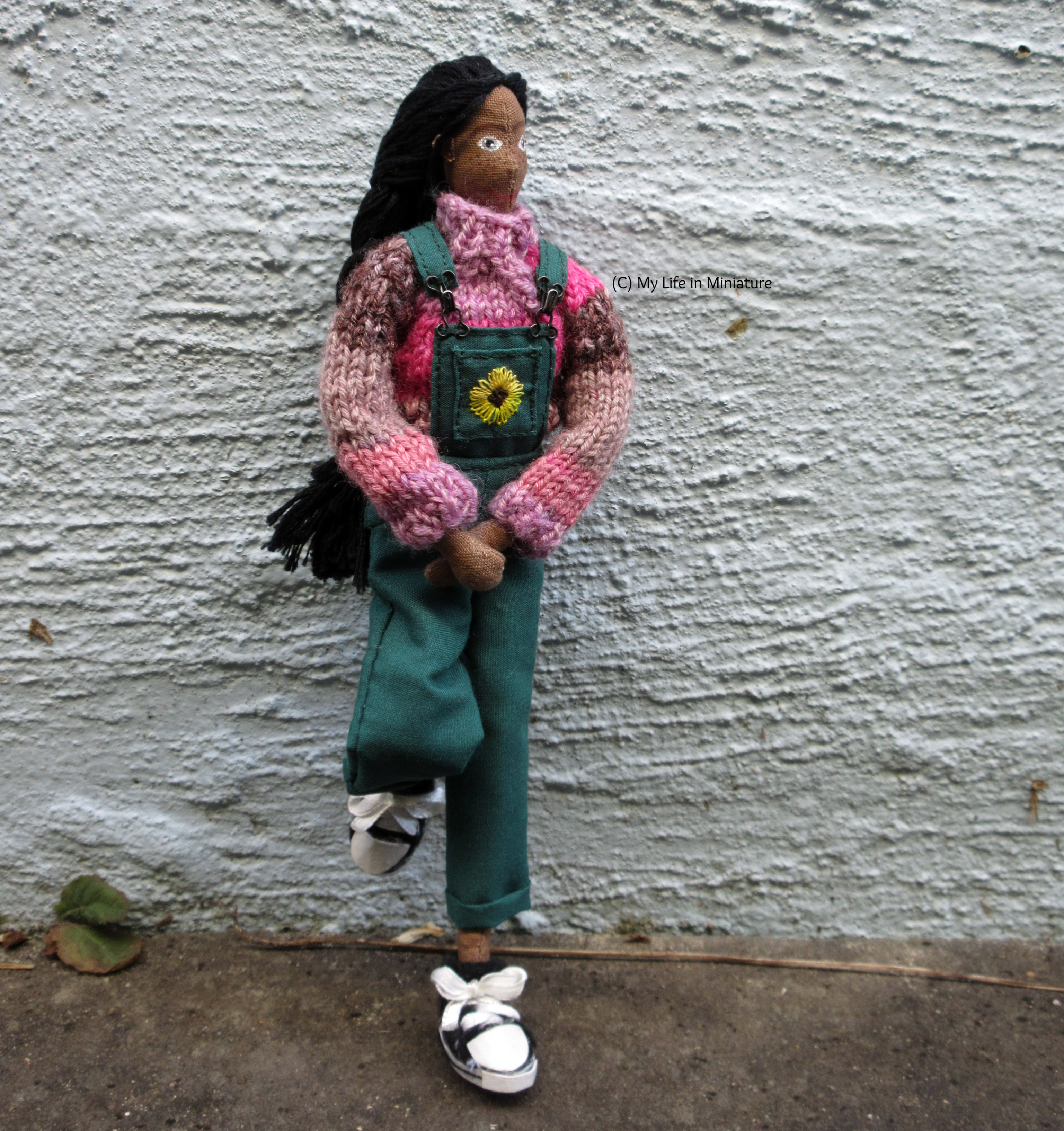 Petra wears the pink jumper, green dungarees, and black shoes against an outdoor textured wall. She has one foot up on the wall, and her hands in front of her. She looks to the right.