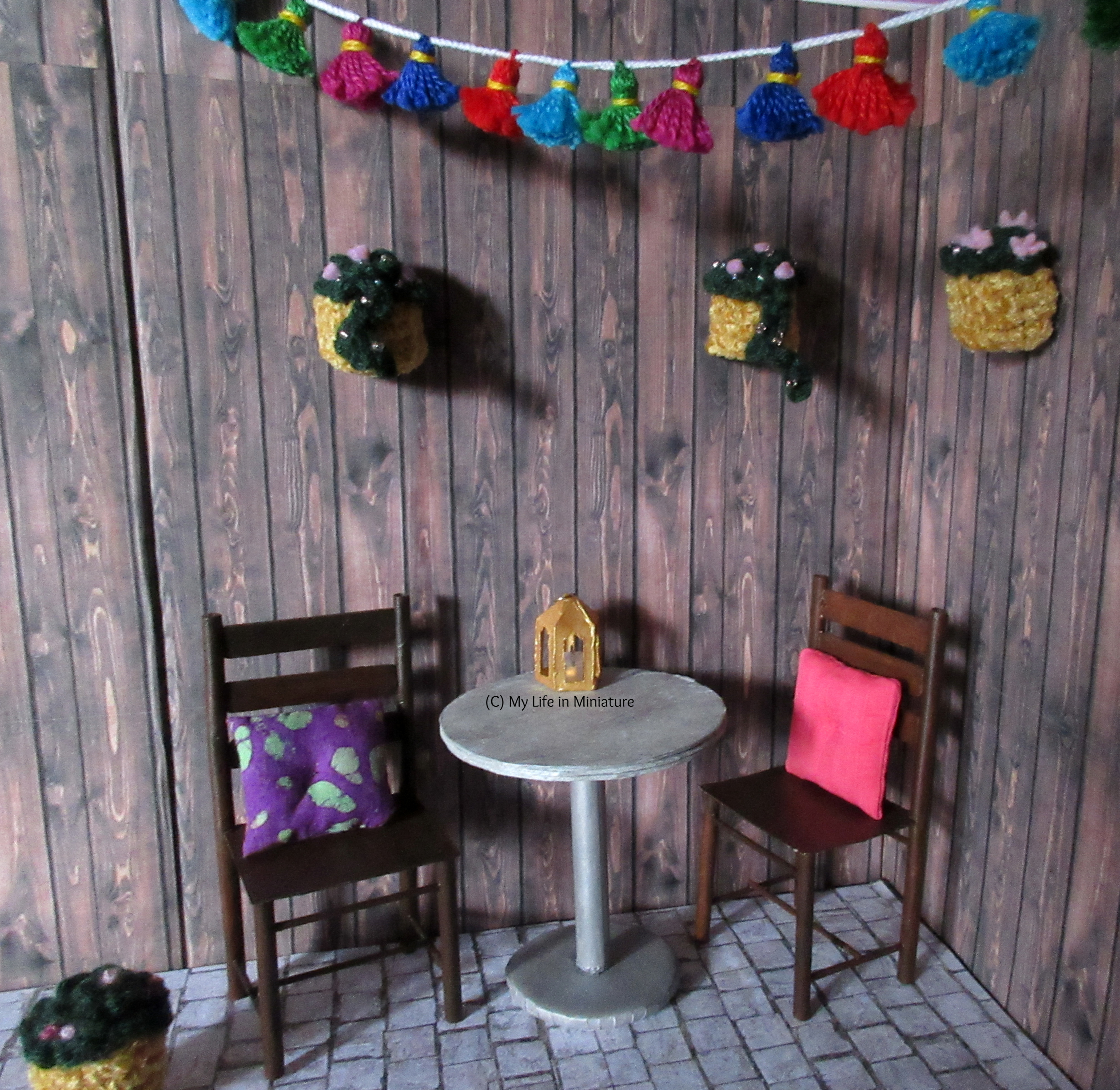 The Tea at Yaz's courtyard is shown, with the addition of three crocheted hanging baskets attached to the walls. The baskets hang above the table and chairs, and below the tassel garland.