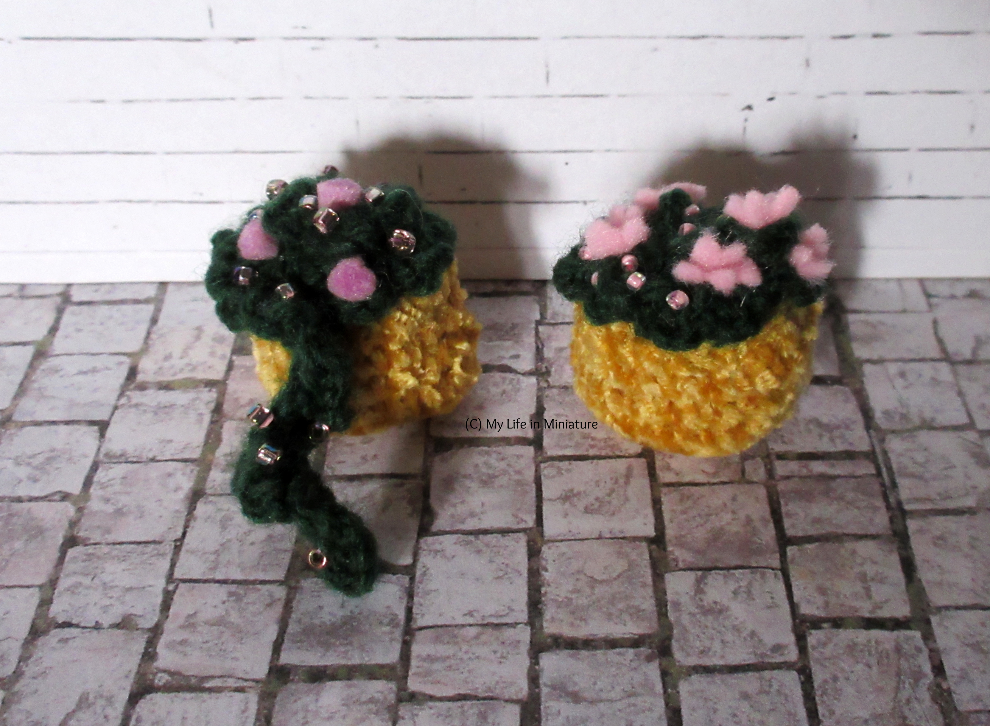 Two of the baskets are against a white brick background. One has purple flowers and beads in, with one stem (?) dangling over. The other has larger pink flowers and beads in. The pots are yellow.