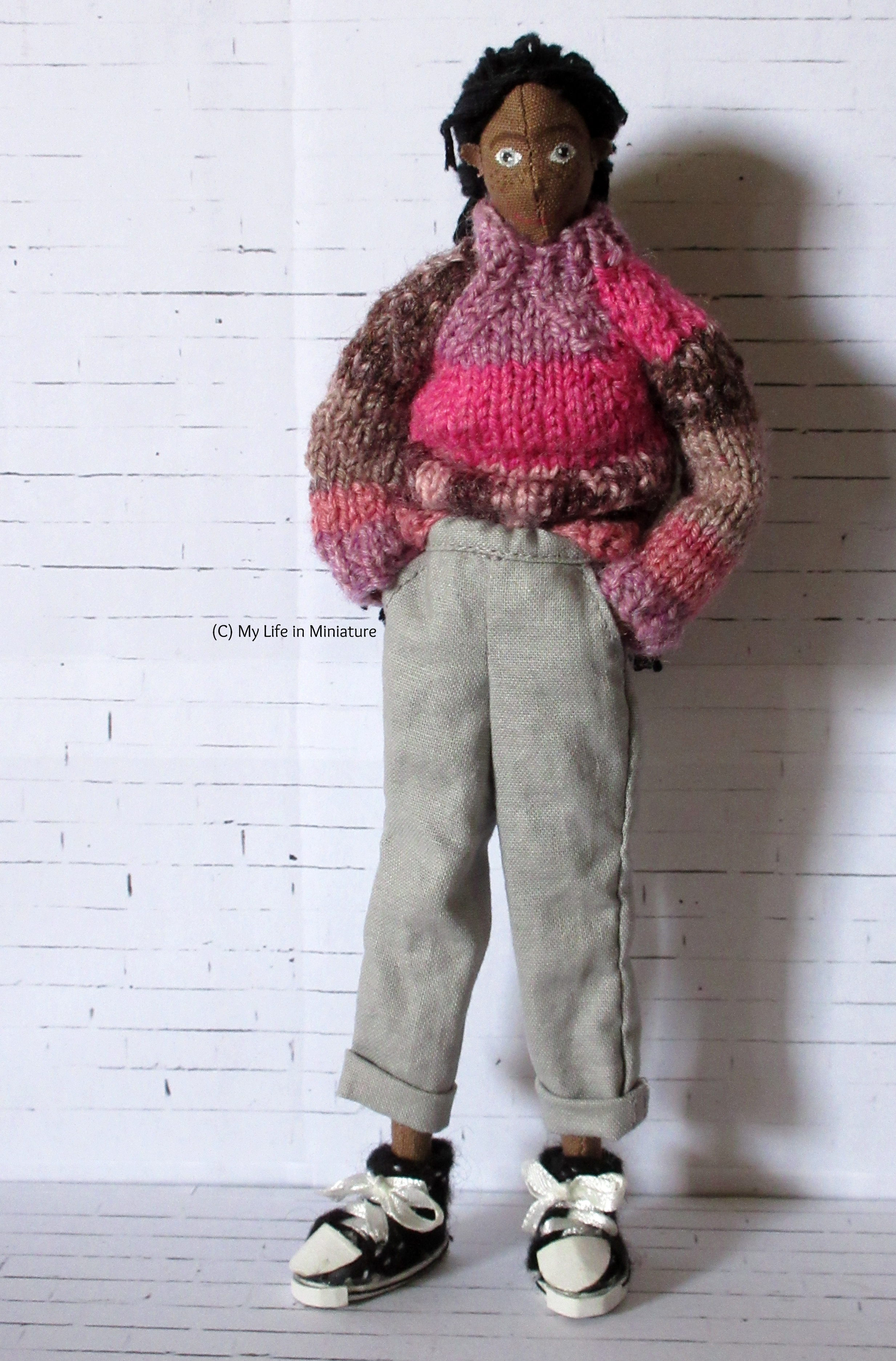 Petra stands against a white brick background. She wears loose pale grey pants, rolled up at the hem, with her pink jumper. Her hands are in her pockets, and she looks at the camera.