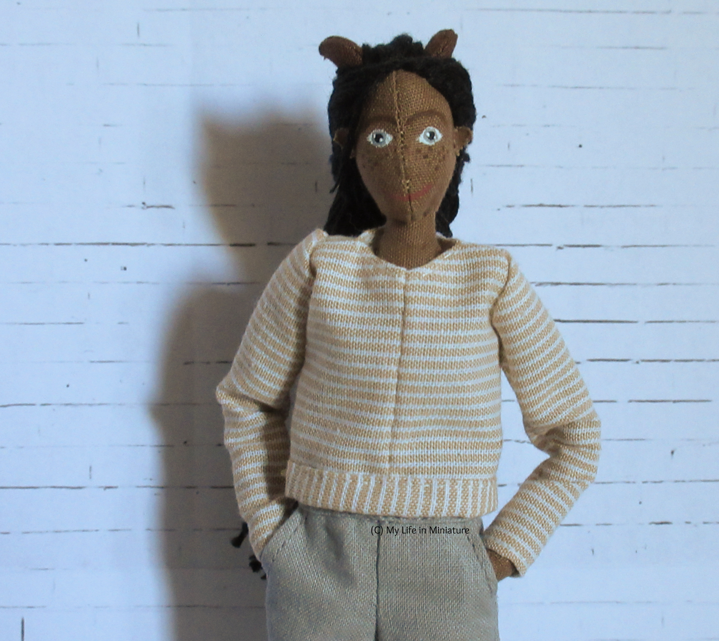 Petra wears a long-sleeved top with her grey pants, hands in pockets. The top is cream-and-white striped, and has a circular neck.