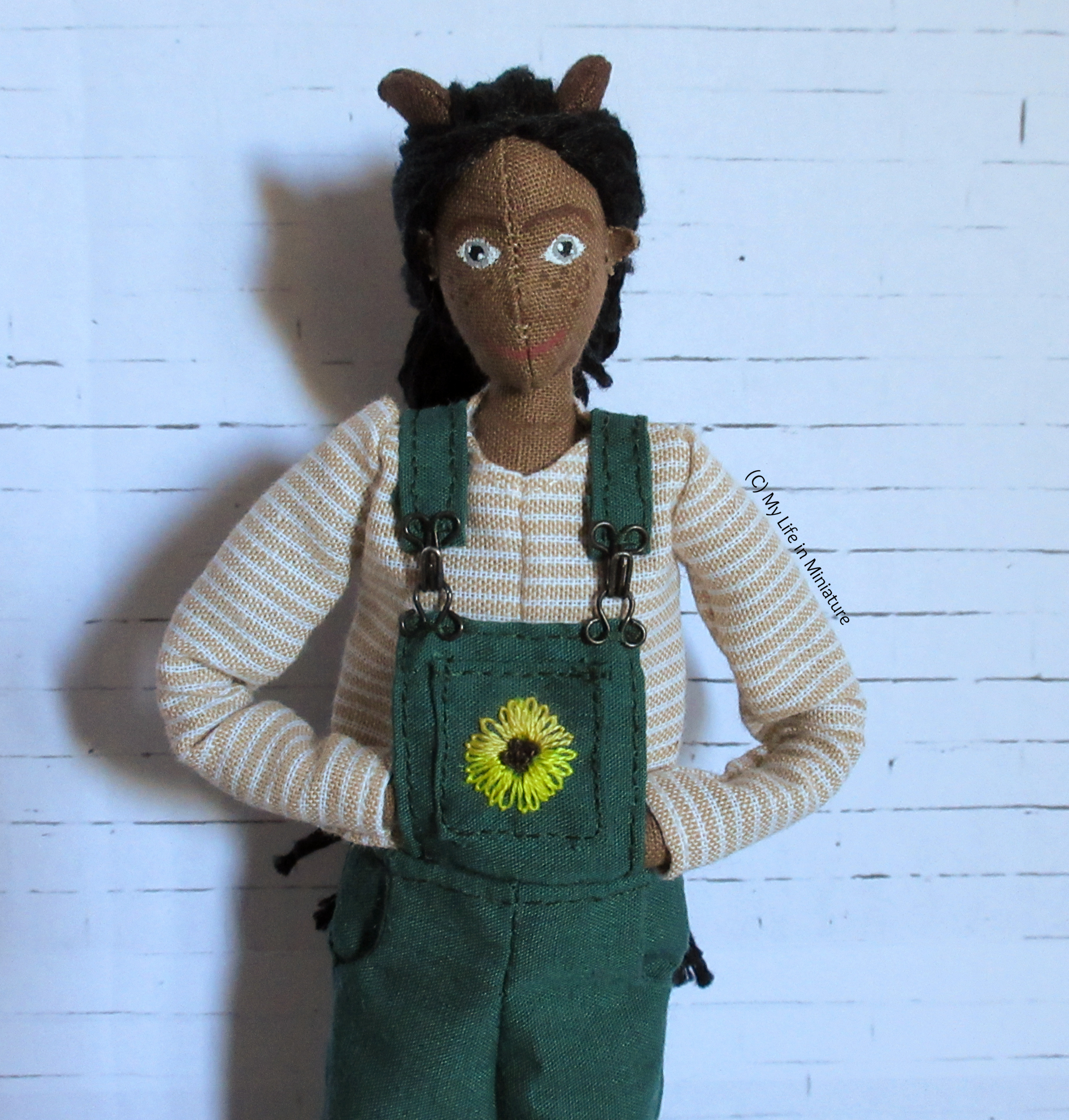 Petra wears the long-sleeved top under her green dungarees, with her hands behind the front bib. She looks at the camera.