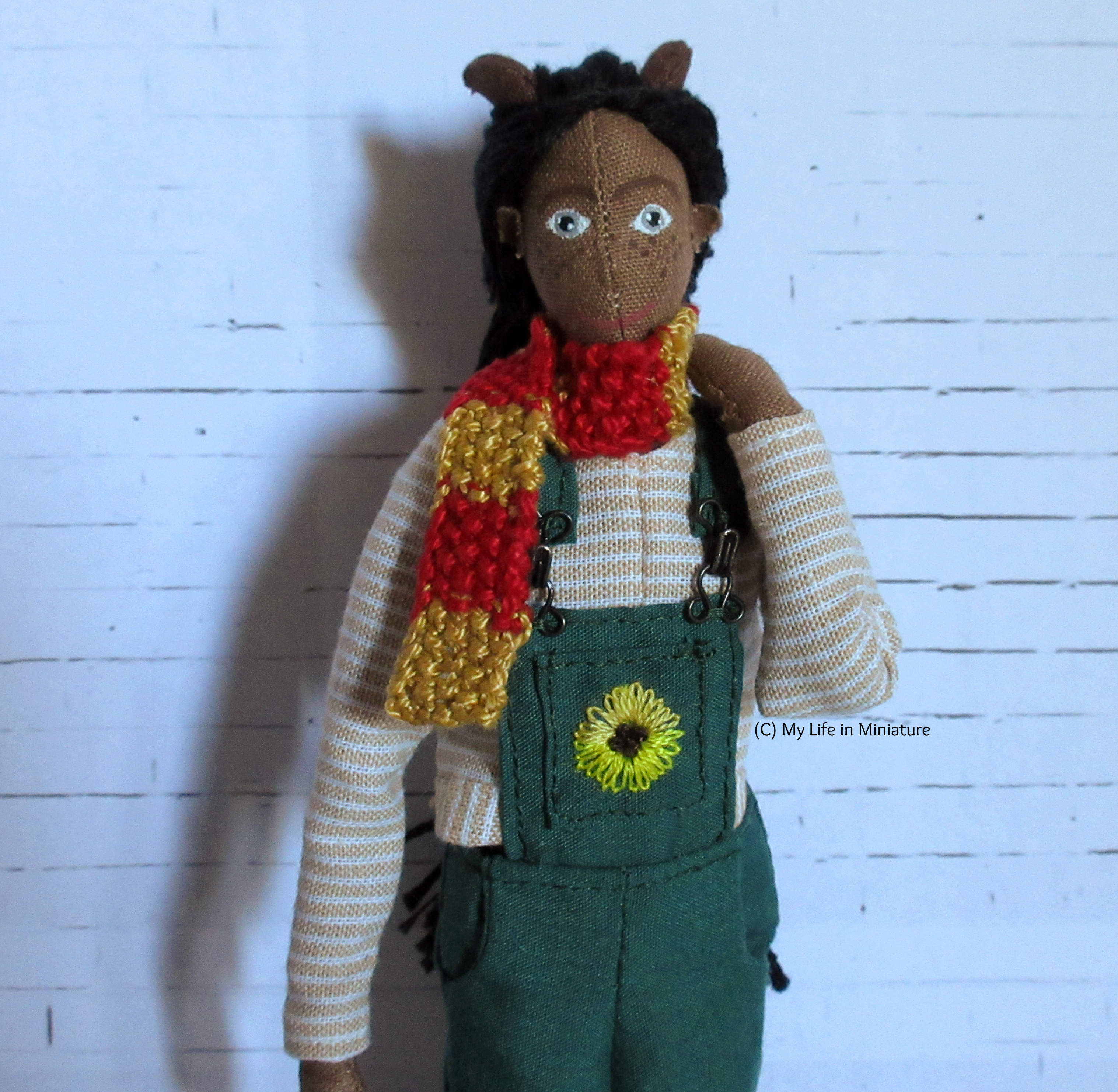 Petra wears the long-sleeved top with her green dungarees and a red-and-gold striped knitted scarf. One hand is on her shoulder, and she smiles at the camera.