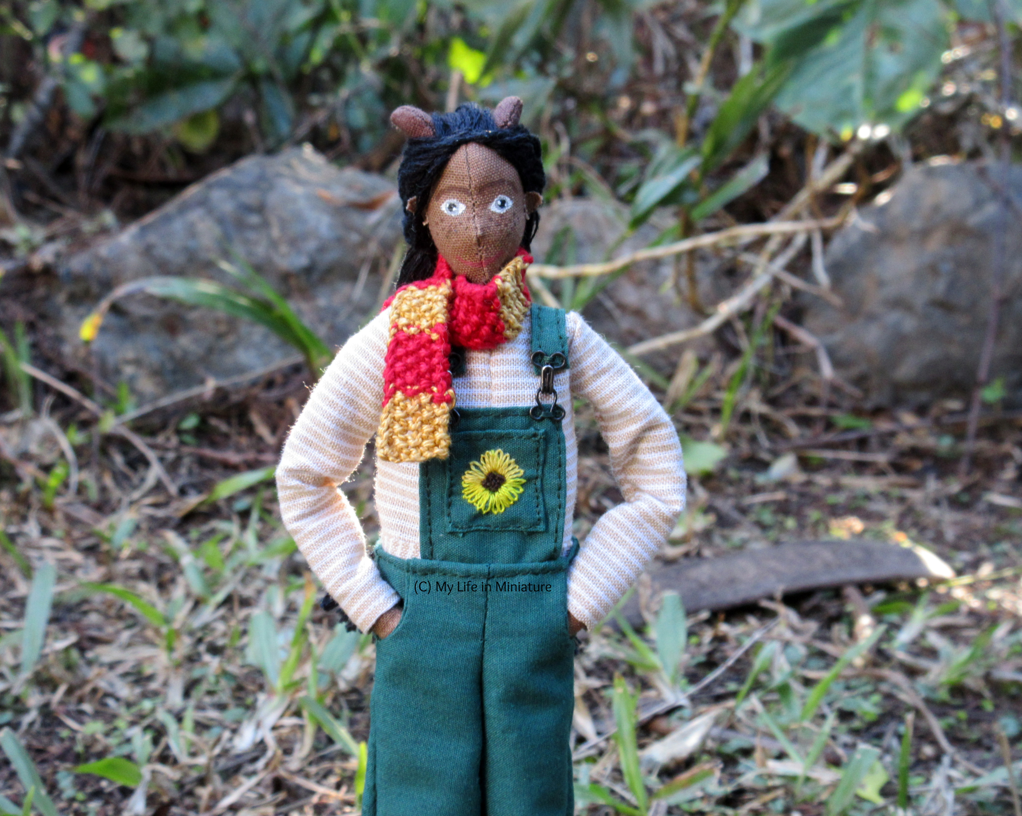Petra stands outside with grass and greenery behind her. She wears the long-sleeved top, her green dungarees, and a knitted red-and-gold scarf. Her hands are in her pockets.