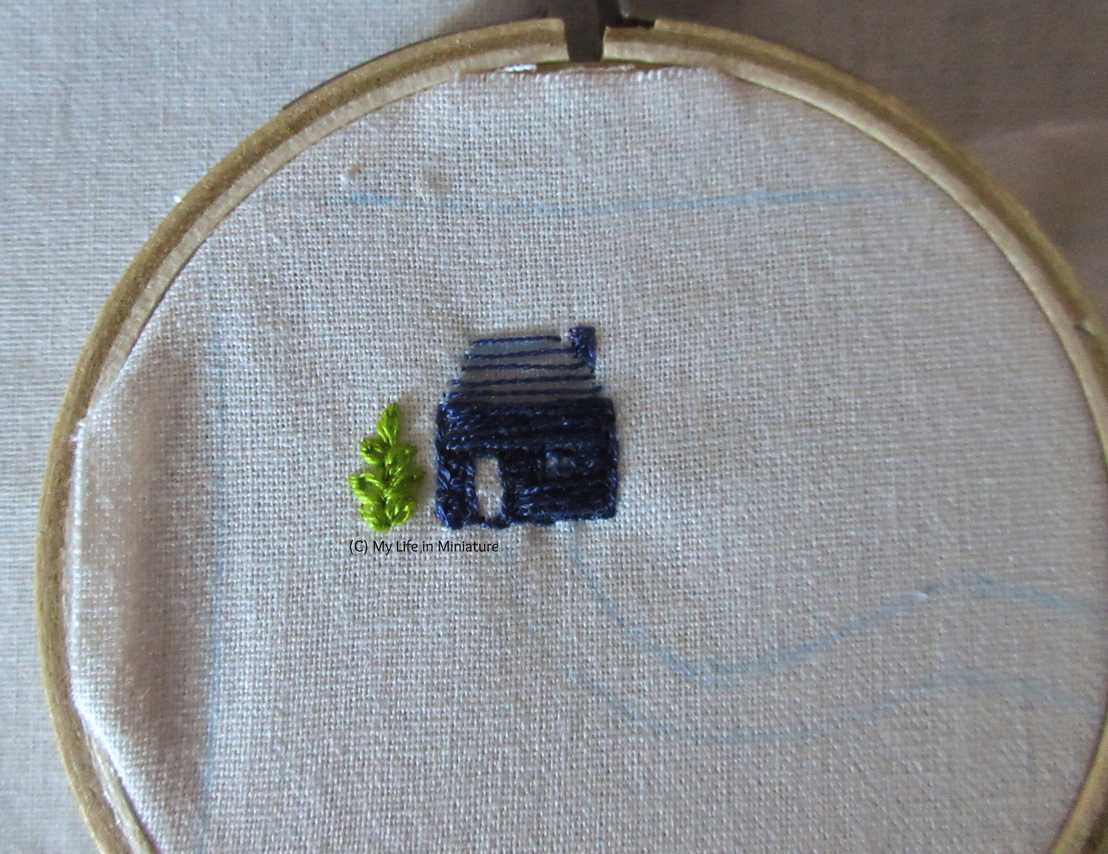 White fabric is in a wooden embroidery hoop. A small navy blue house and a green plant are embroidered on it, next to each other.