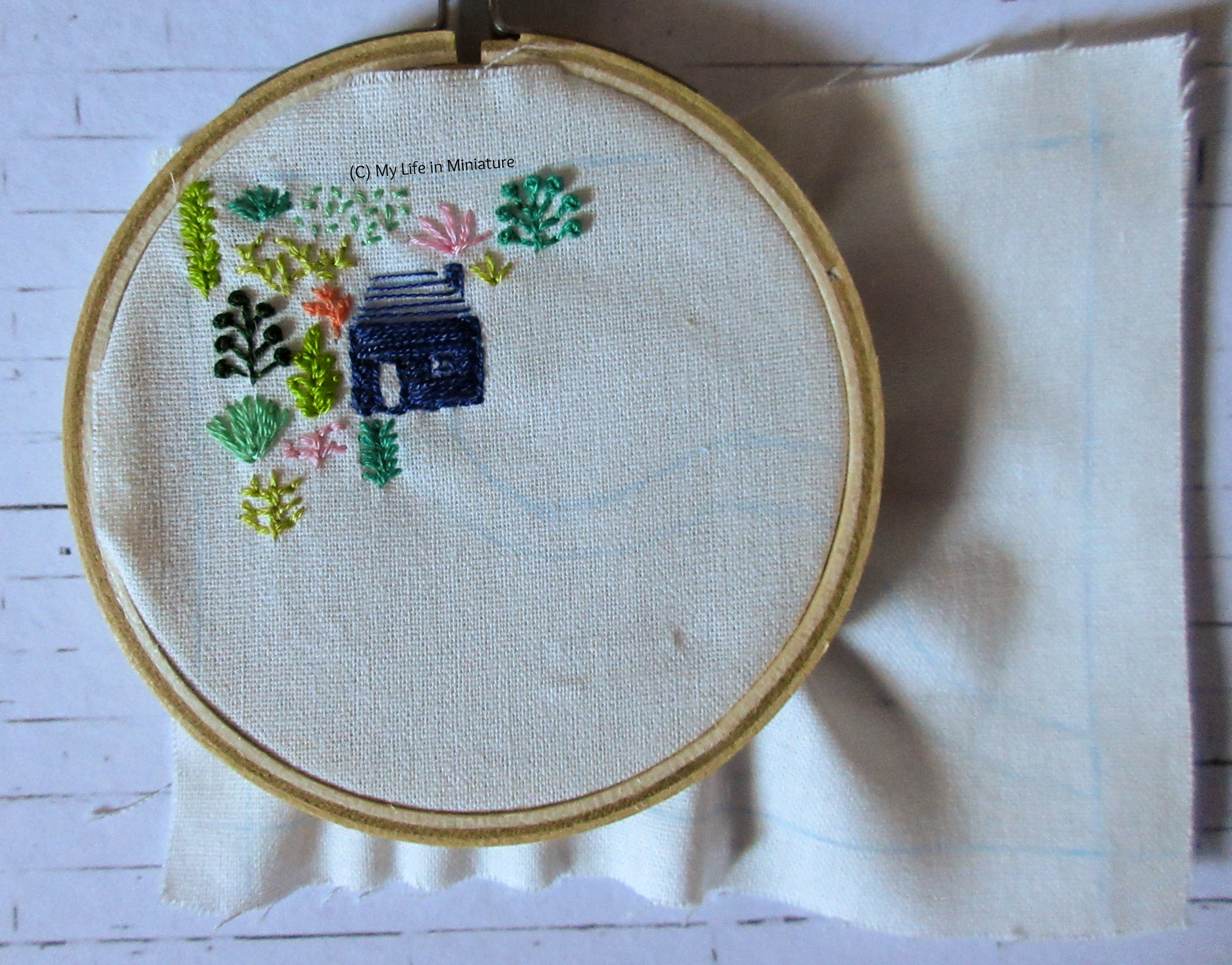 White fabric is in an embroidery hoop. Stitched on it is a small navy blue house, and an assortment of plants in different colours. All this is in the top left corner of the fabric.