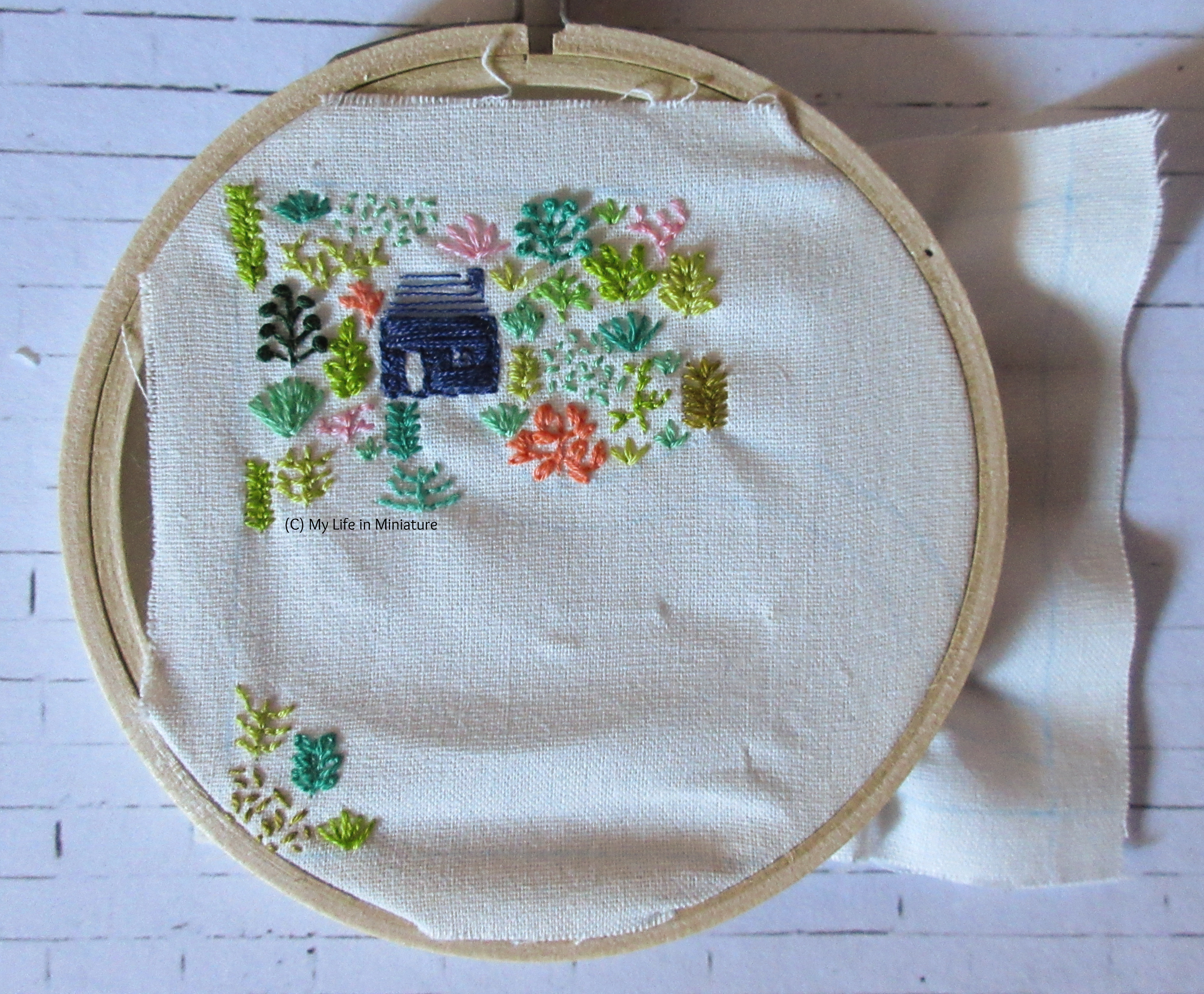 White fabric is in an embroidery hoop. Stitched on it is a small navy blue house, and an assortment of plants in different colours. Most of the plants and the house are in the top-left of the fabric, and the rest are in the bottom-left corner.