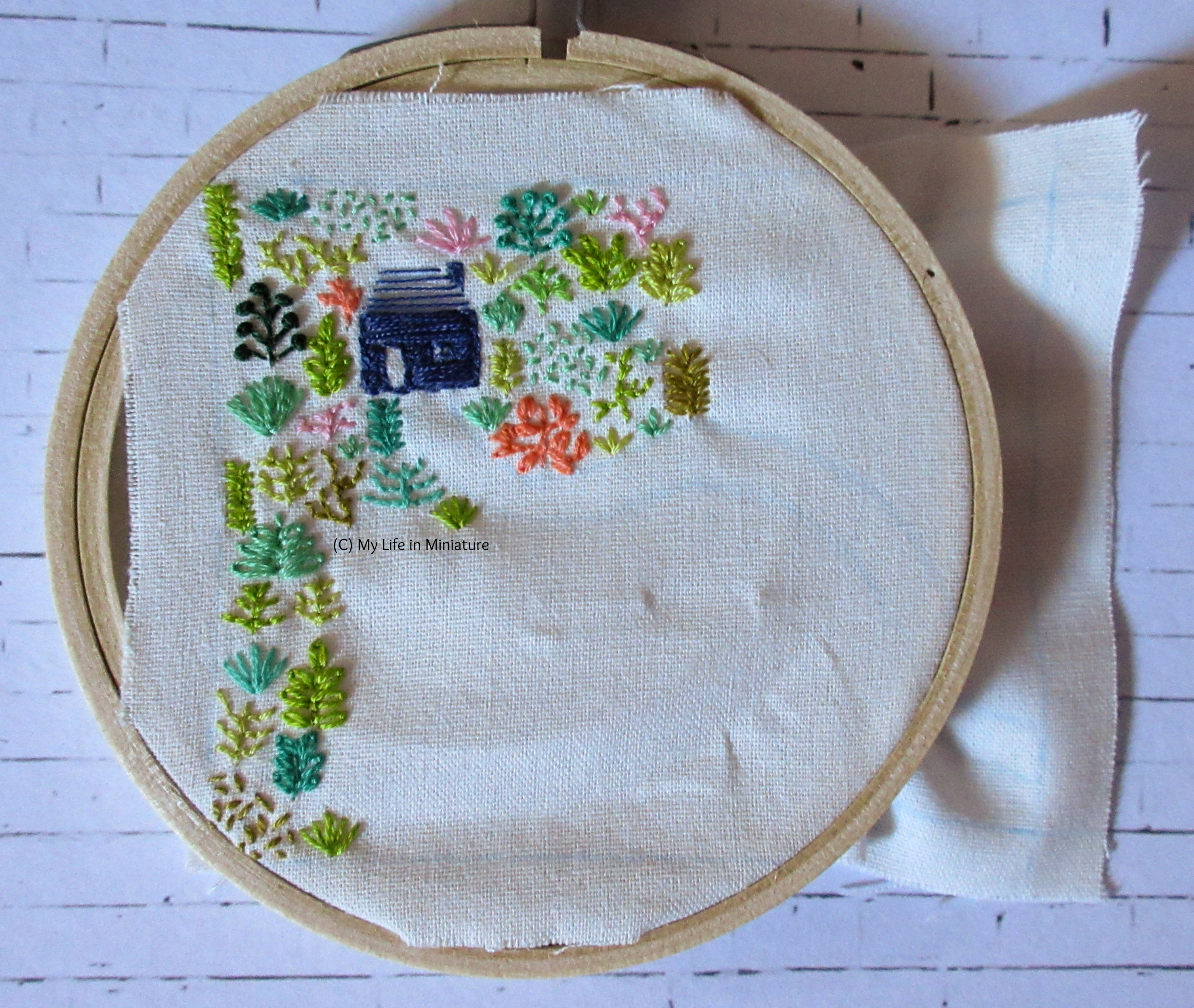 White fabric is in an embroidery hoop. Stitched on it is a small navy blue house, and an assortment of plants in different colours. All the stitching is towards the left-hand-side of the fabric. A white path is starting to emerge, curving from the front of the house.