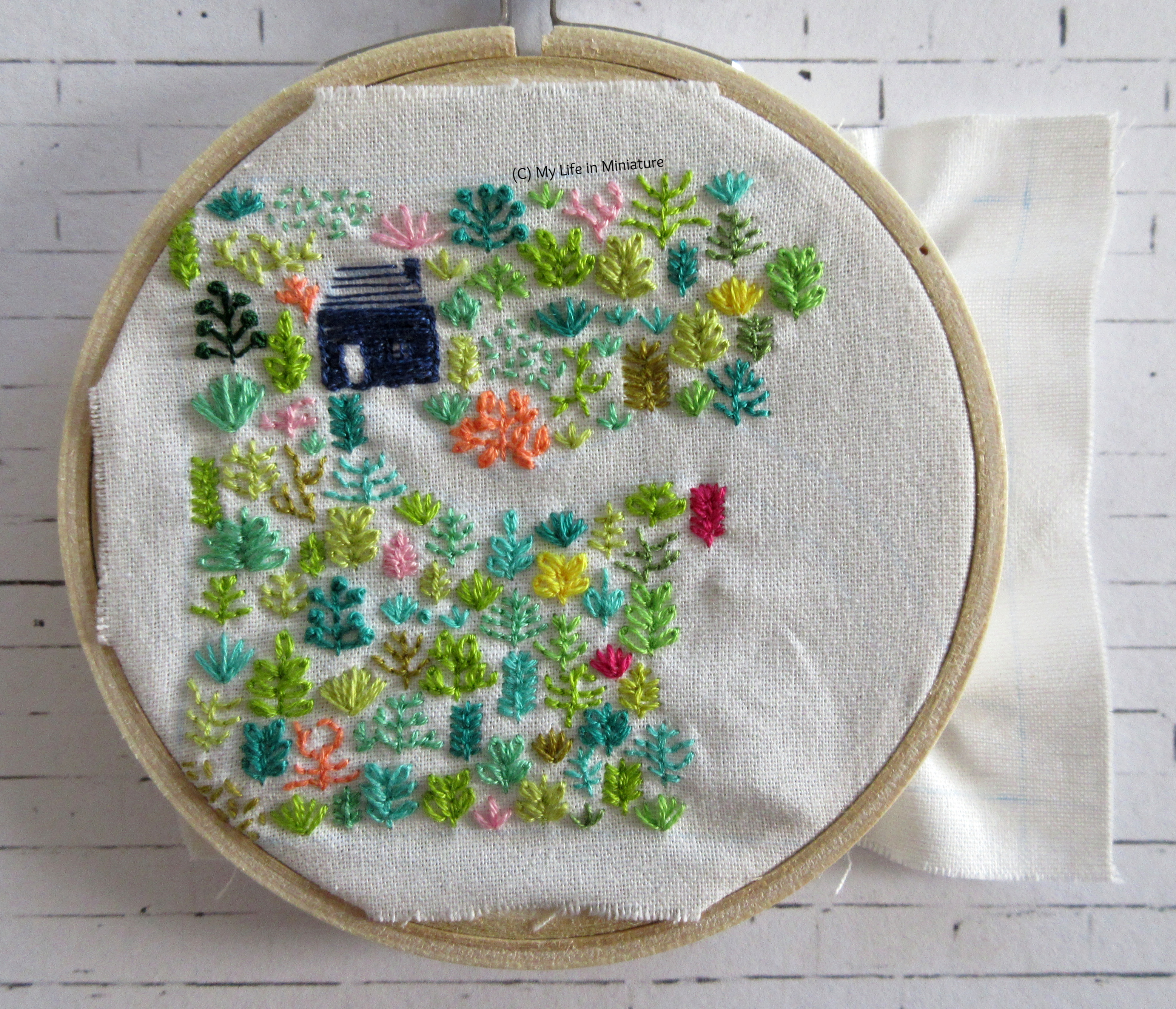 White fabric is in an embroidery hoop. Stitched on it is a small navy blue house, and an assortment of plants in different colours. The plants cover most of the fabric in the hoop, and a winding path leading from the house is visible.