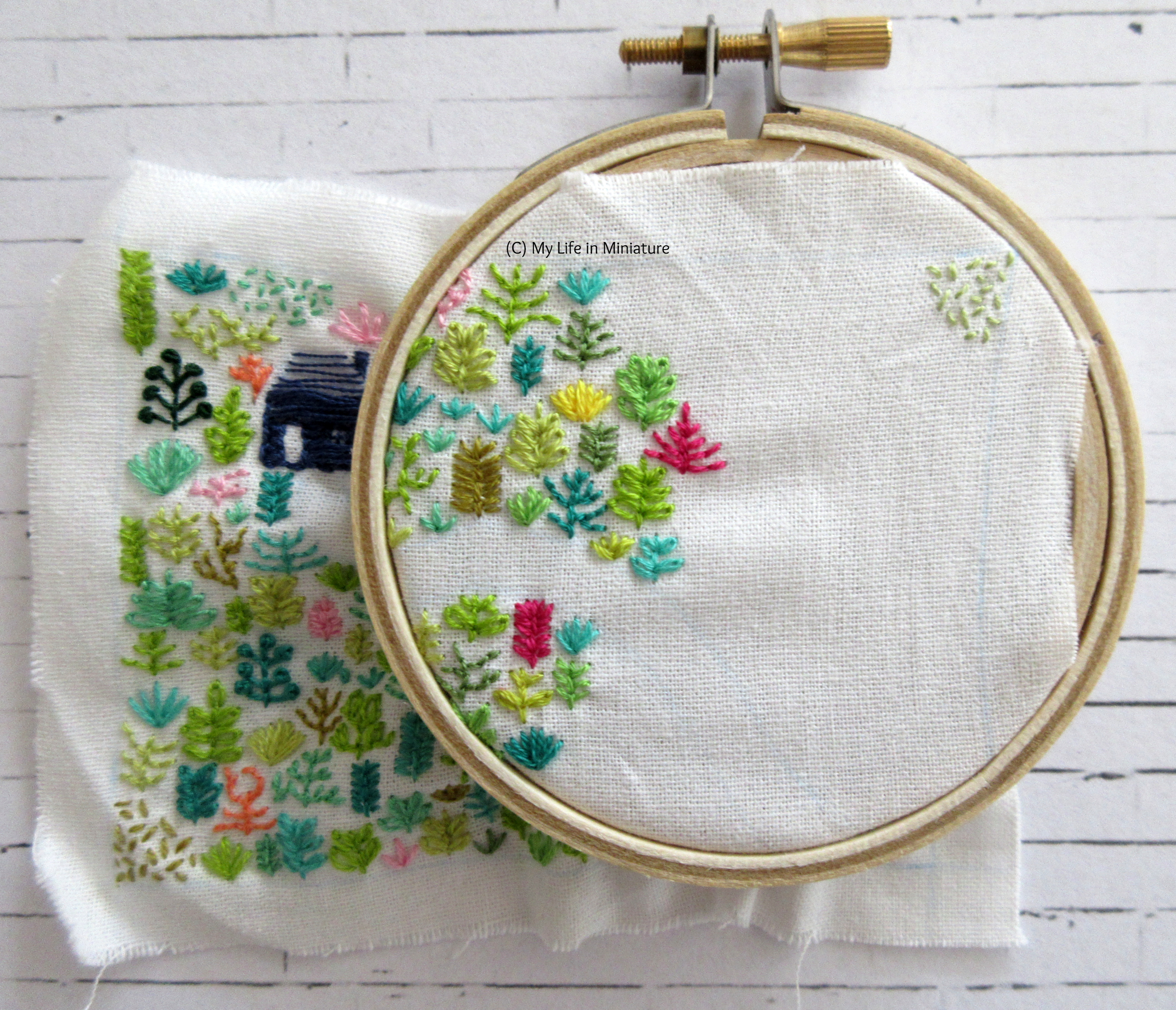 White fabric is in an embroidery hoop. Stitched on it is a small navy blue house, and an assortment of plants in different colours. The hoop is in the top-right corner of the fabric, and it's partially filled with plants.