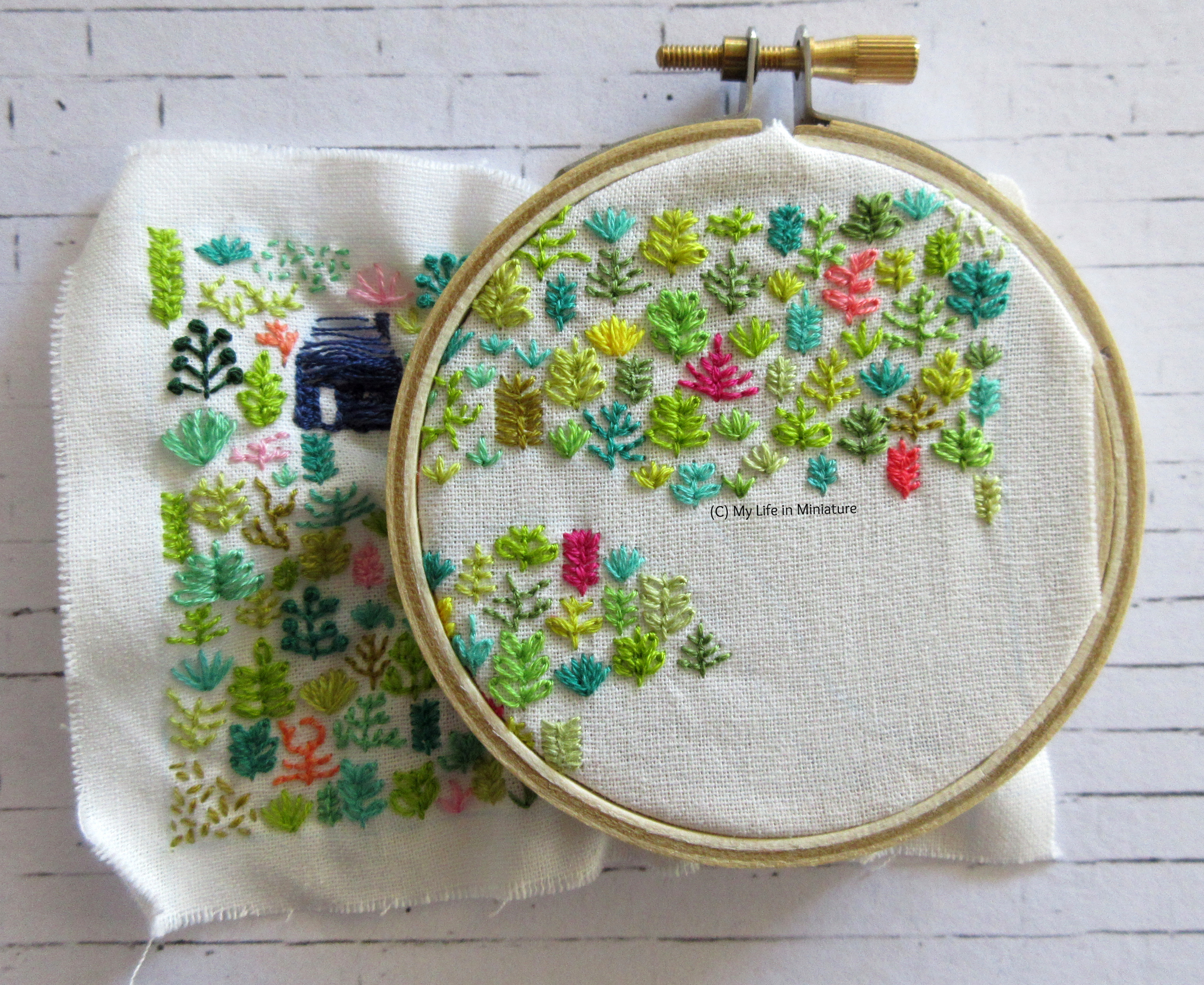 White fabric is in an embroidery hoop. Stitched on it is a small navy blue house, and an assortment of plants in different colours. The hoop is in the top-right of the fabric, and is about half-full of plants.