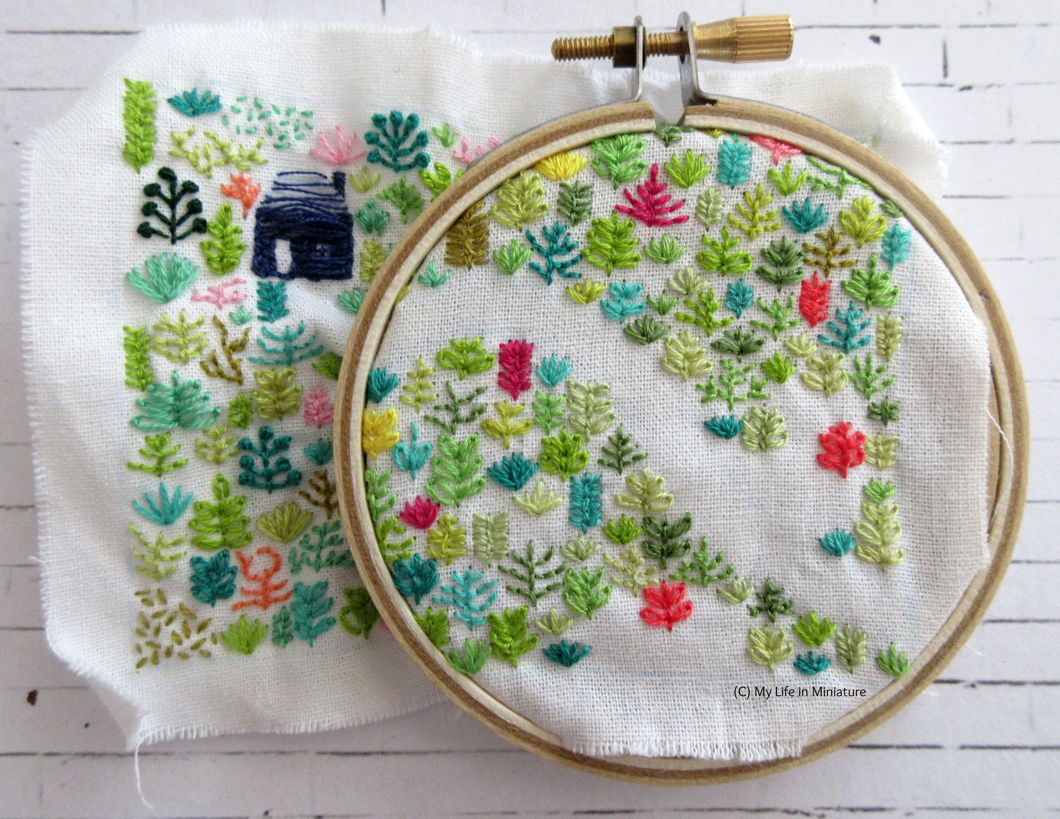 White fabric is in an embroidery hoop. Stitched on it is a small navy blue house, and an assortment of plants in different colours. The hoop is in the top-right of the fabric, and is nearly full of plants.