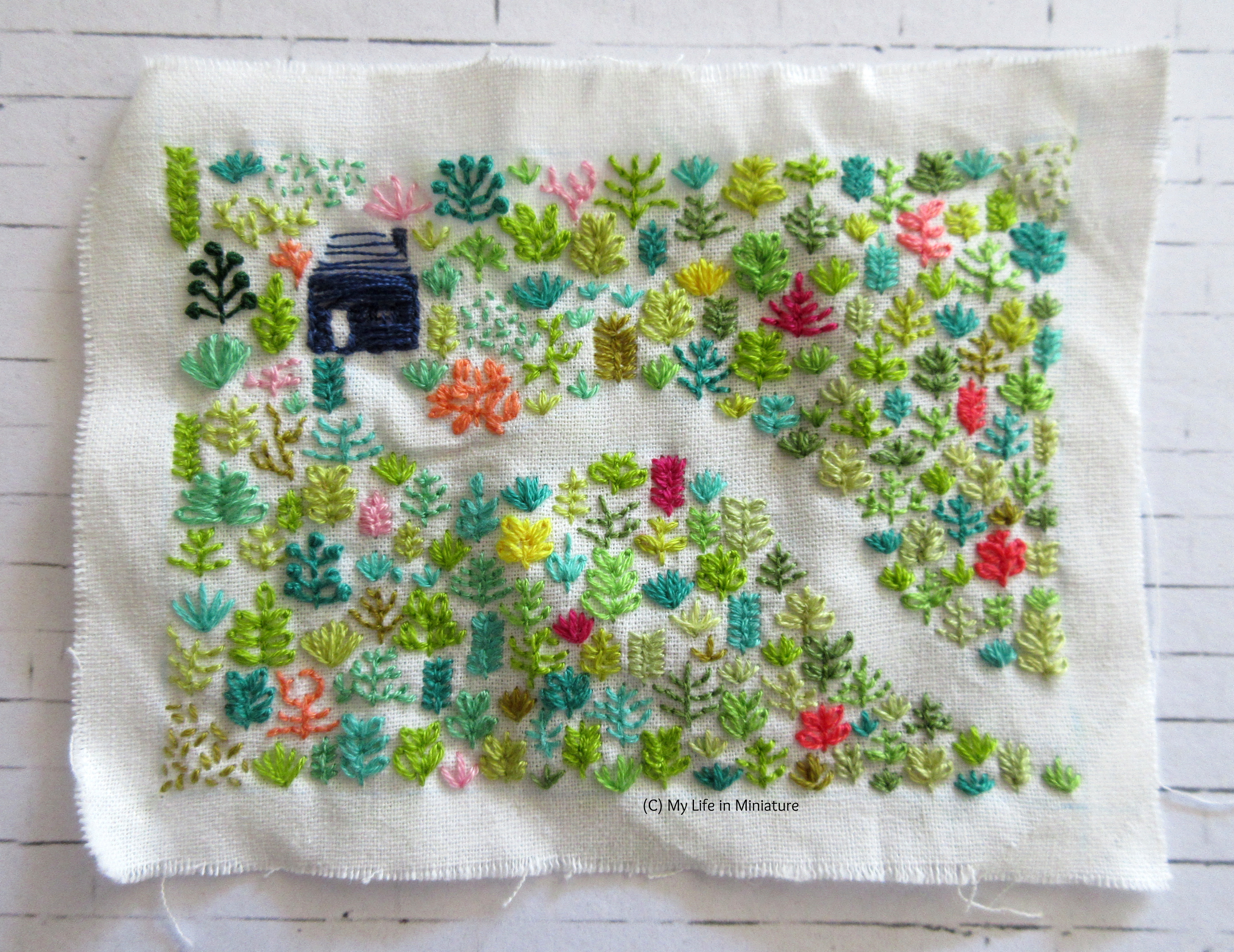 A square of white fabric sits on a white background. Embroidered on it is a navy blue house, surrounded by plants that also line a path, curving towards the bottom-right.