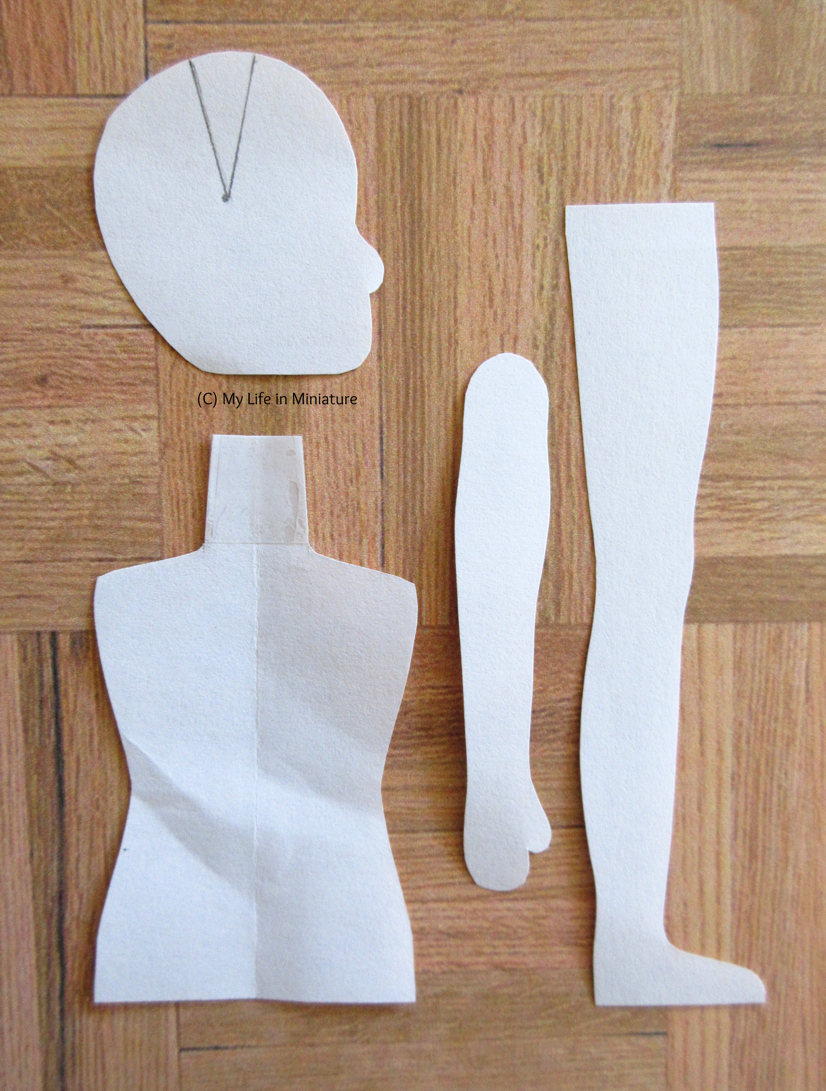 A paper pattern for a doll sits on a wood parquet background. Pieces for a head, arm, leg, and torso are visible.