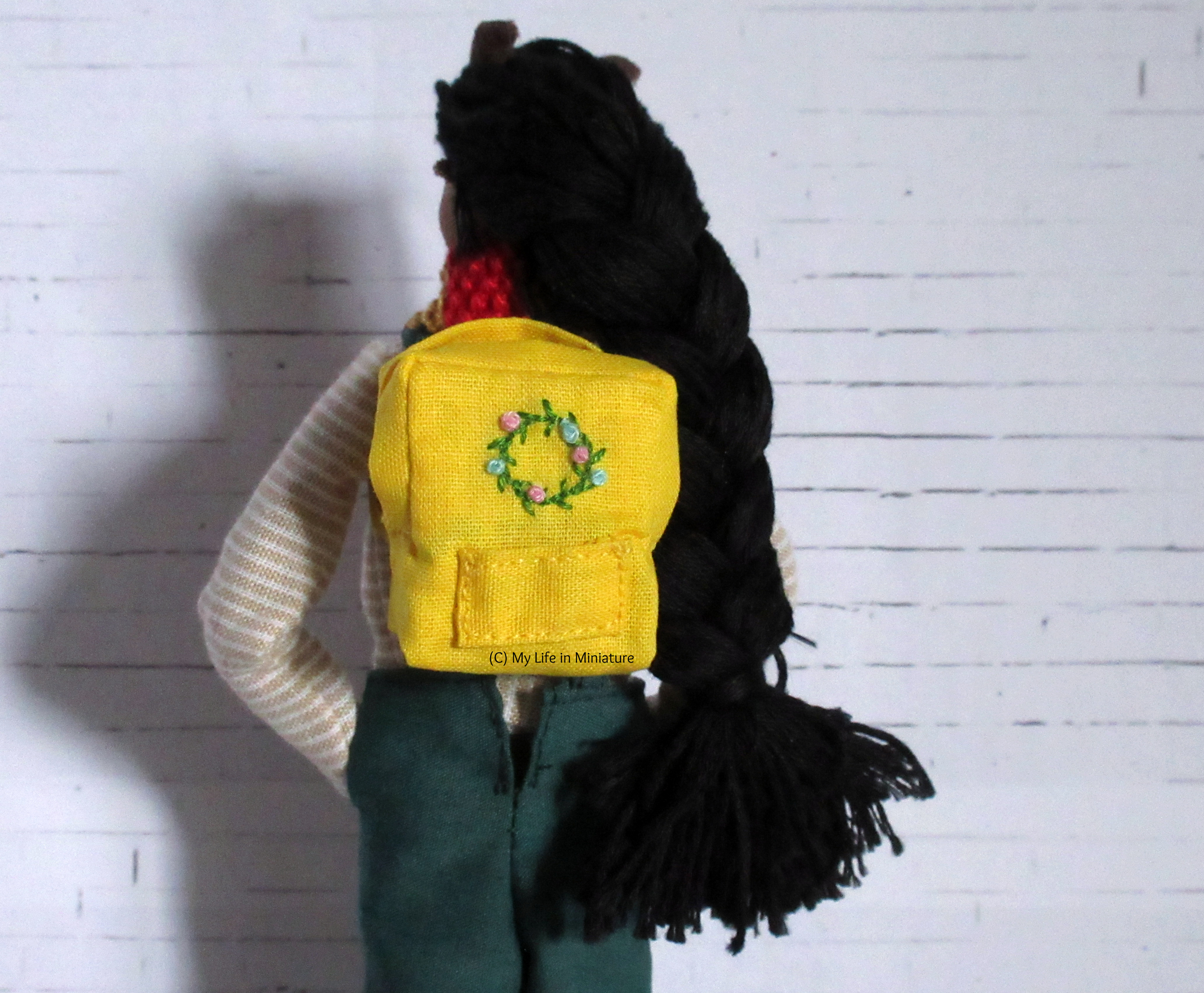 Petra faces away from the camera against a white brick background. On her back is a yellow square backpack with a pocket and an embroidered floral wreath on the front.