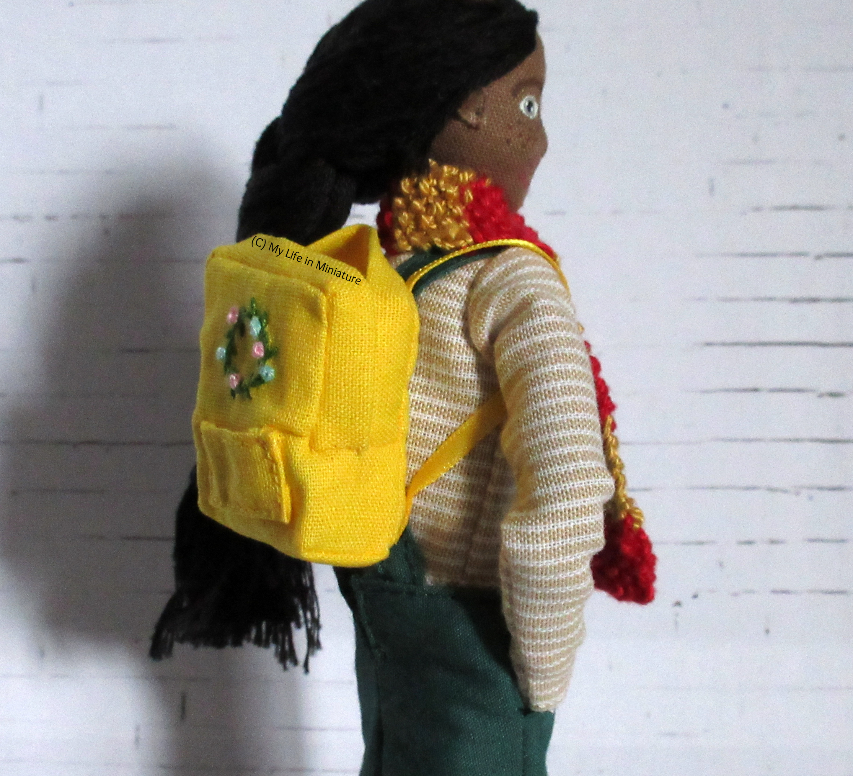 Side-on view of Petra wearing the backpack. The yellow ribbon straps are visible, as well as the side of the backpack.