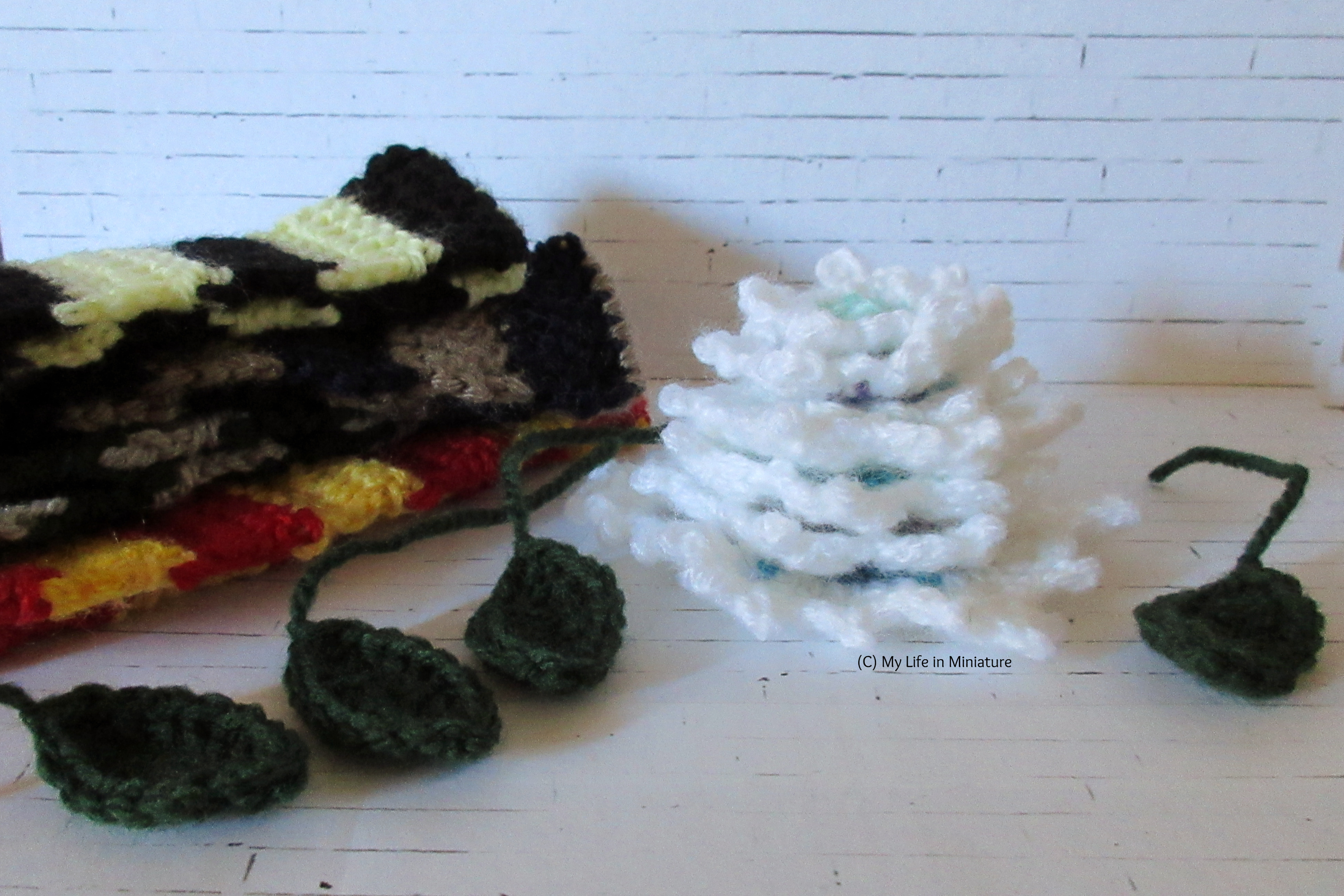 A stack of crocheted snowflakes, small crocheted scarves, and four crocheted green leaves sit against a white brick background.