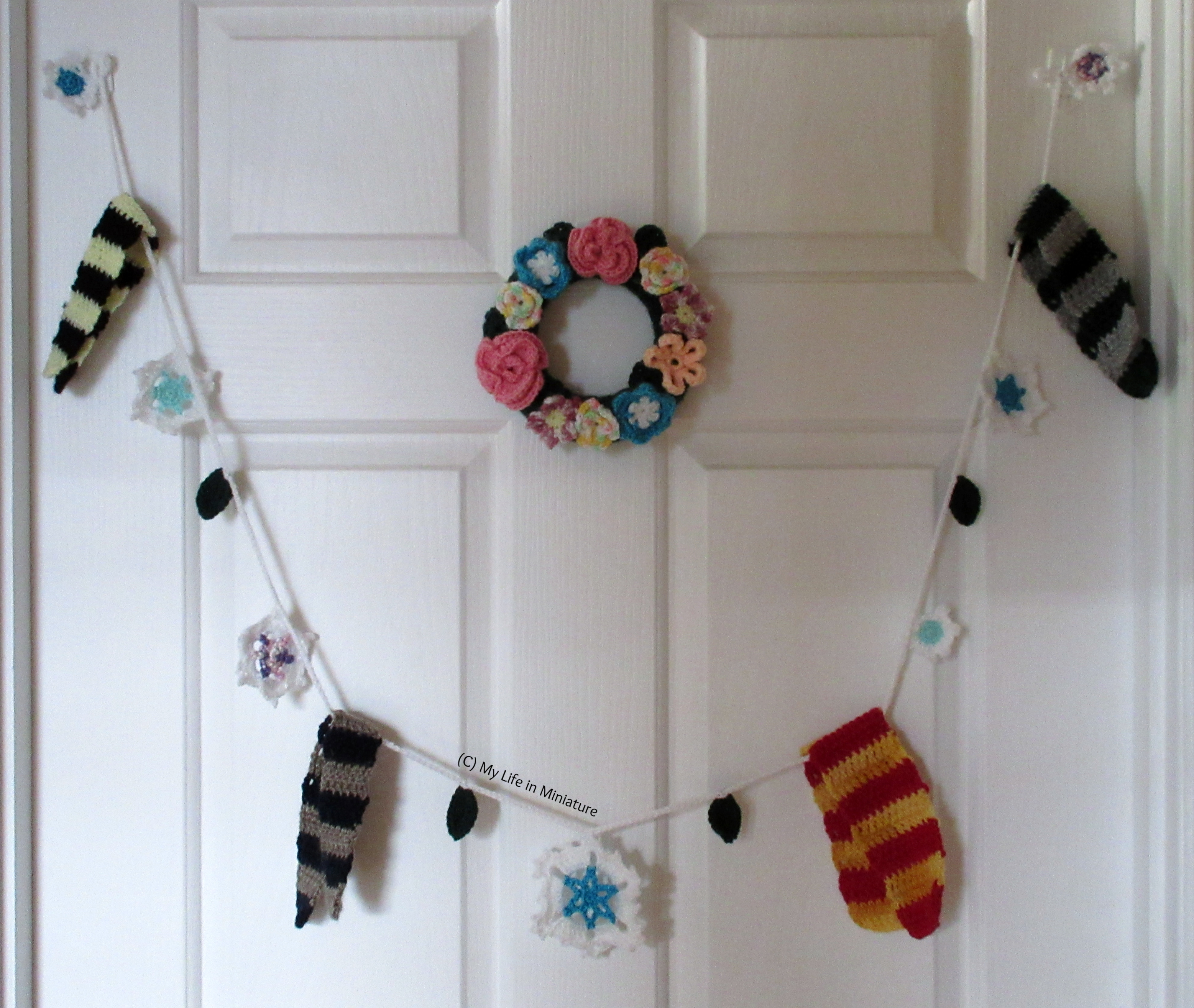 A crocheted garland, made of scarves, snowflakes, and some leaves, hangs on a white door below a small floral crocheted wreath.