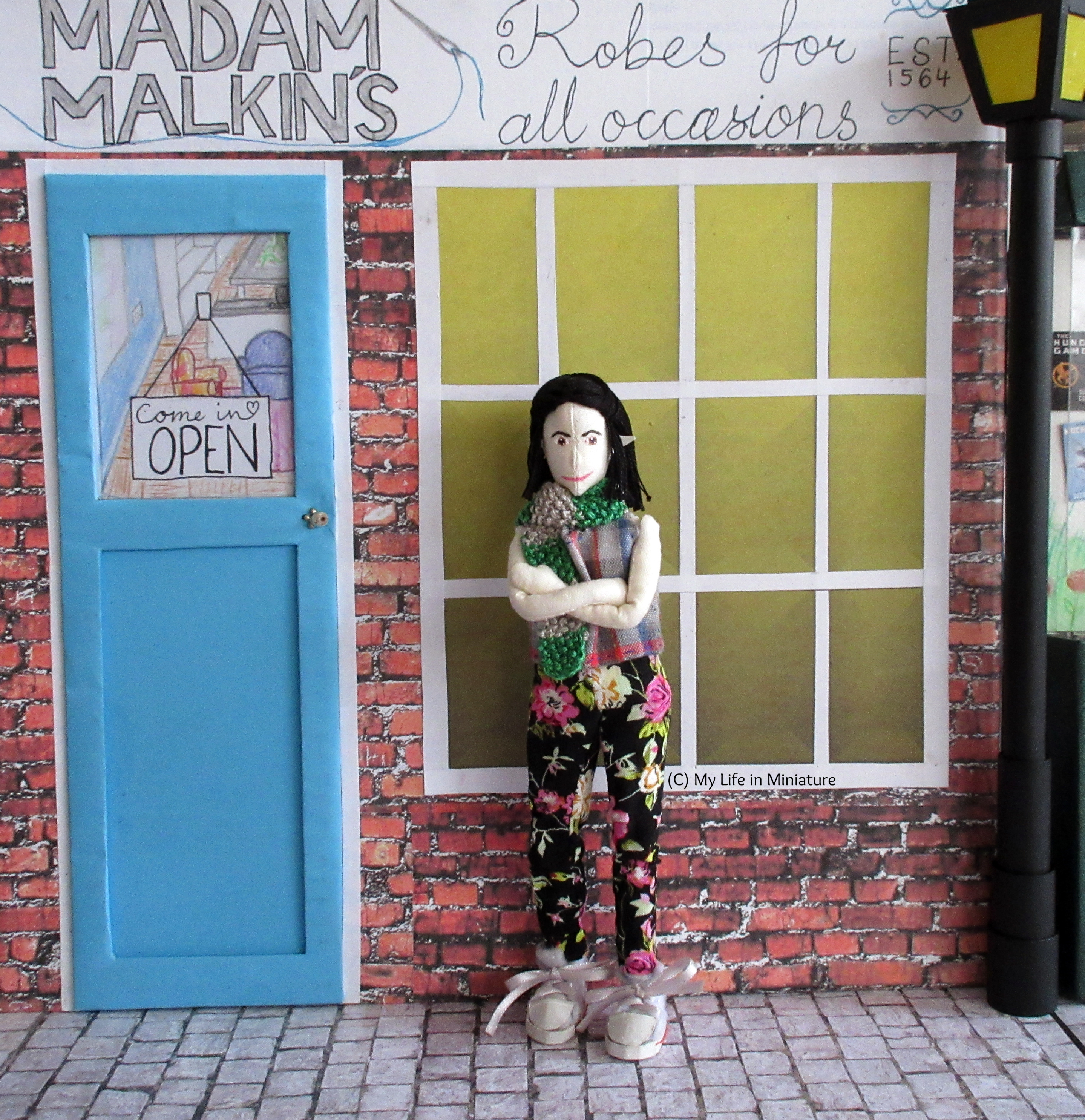 Tiffany stands outside Madam Malkins', smiling at the camera. Her arms are crossed, and she wears a silver-and-green knitted scarf.