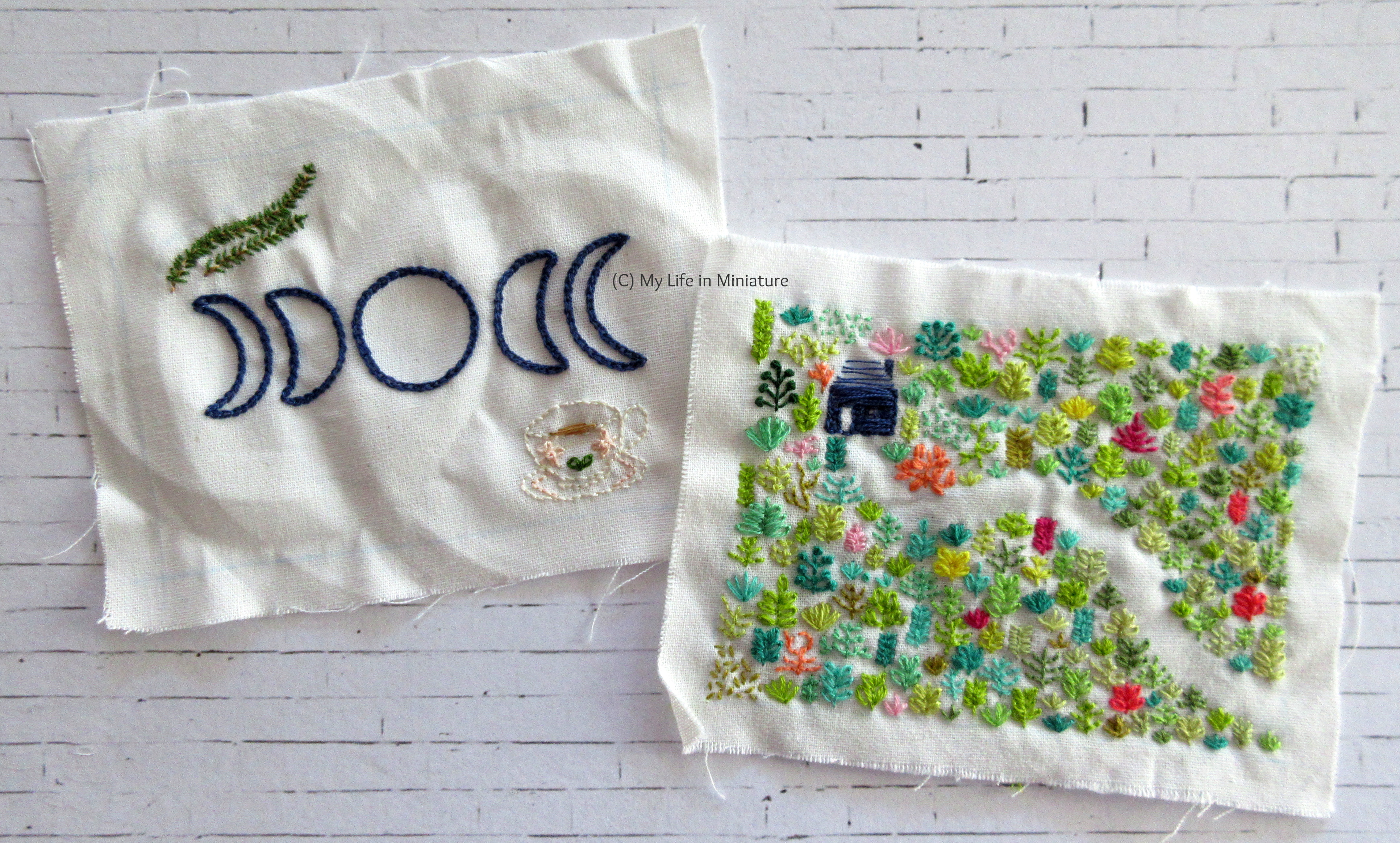 Two squares of white fabric sit on a white brick background. One has a small forest embroidered on, with a small navy blue house in the middle and a path leading to the bottom-right. The other has five moons in navy blue, a teacup, and some rosemary embroidered on.