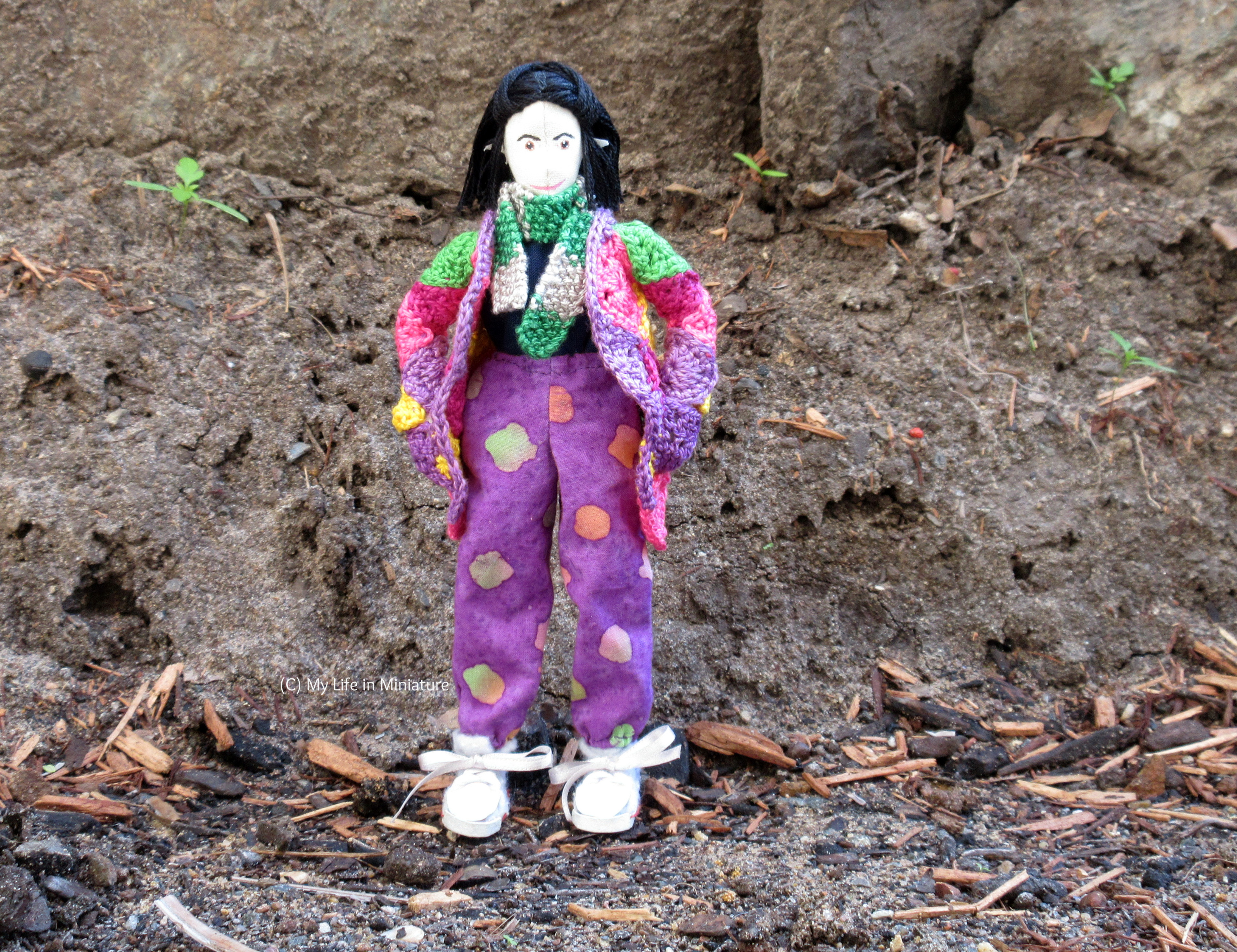 Tiffany stands outside, against a dirt wall. She wears the purple, loose pants with a navy top, her crocheted cardigan, and a scarf. She looks at the camera, hands in cardigan pockets.
