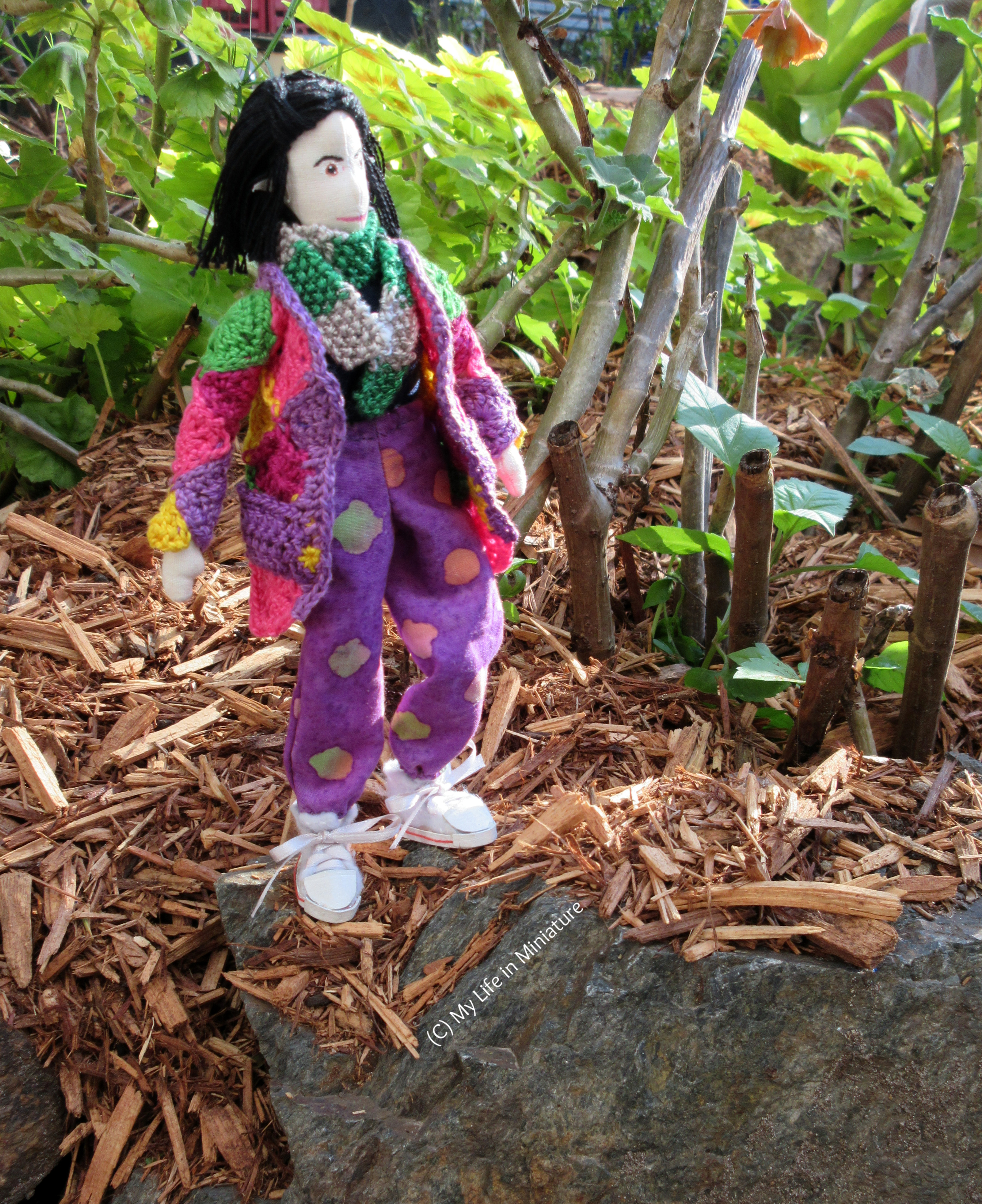 Tiffany stands upon a rock with plants in the background, looking heroically up to the sky. She wears the loose purple pants, crocheted cardigan, and scarf.