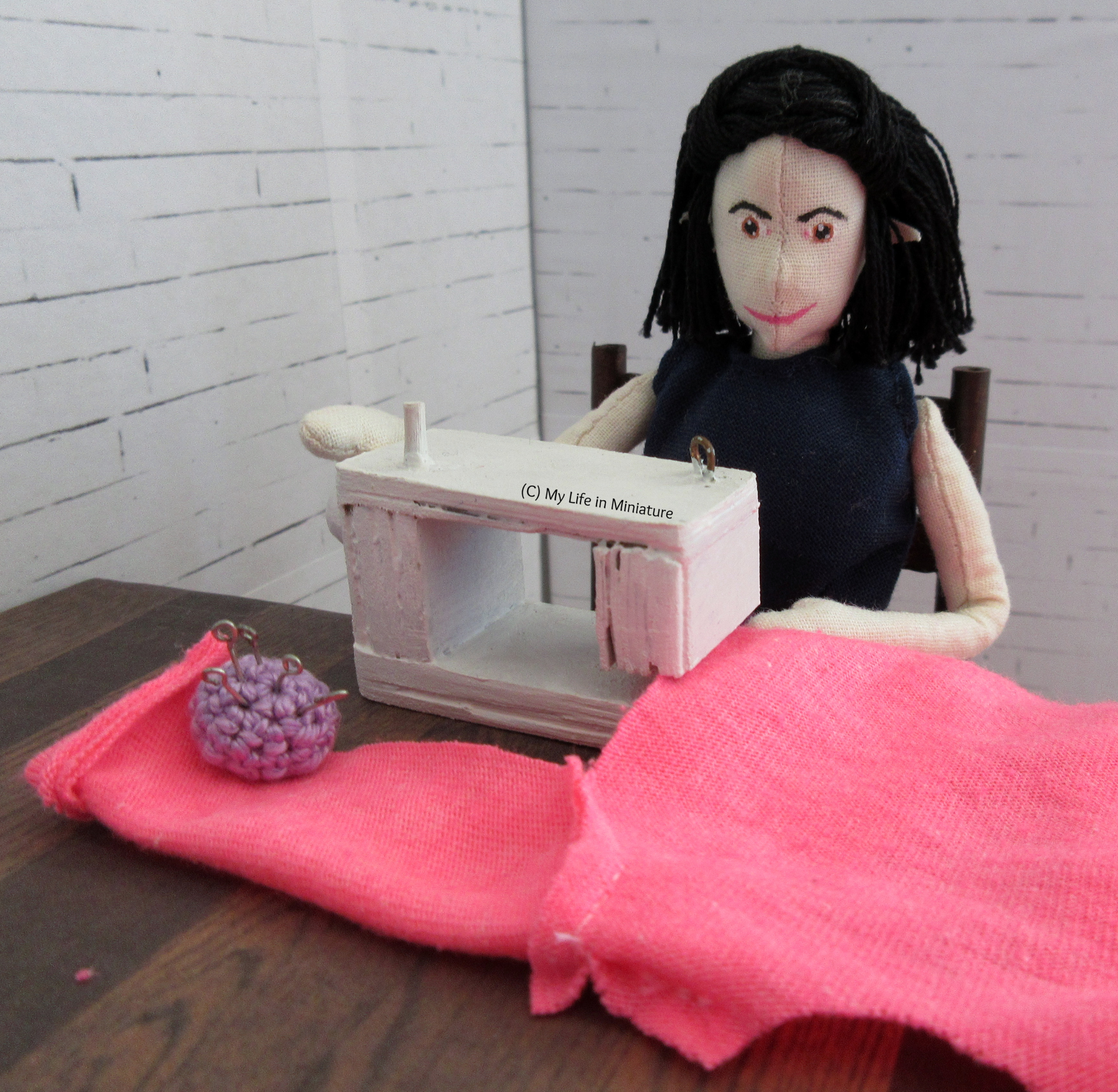 Tiffany sits at her sewing machine, sewing a side seam of the neon pink cardigan. A cuffed sleeve is visible, with a purple pincushion resting on it.