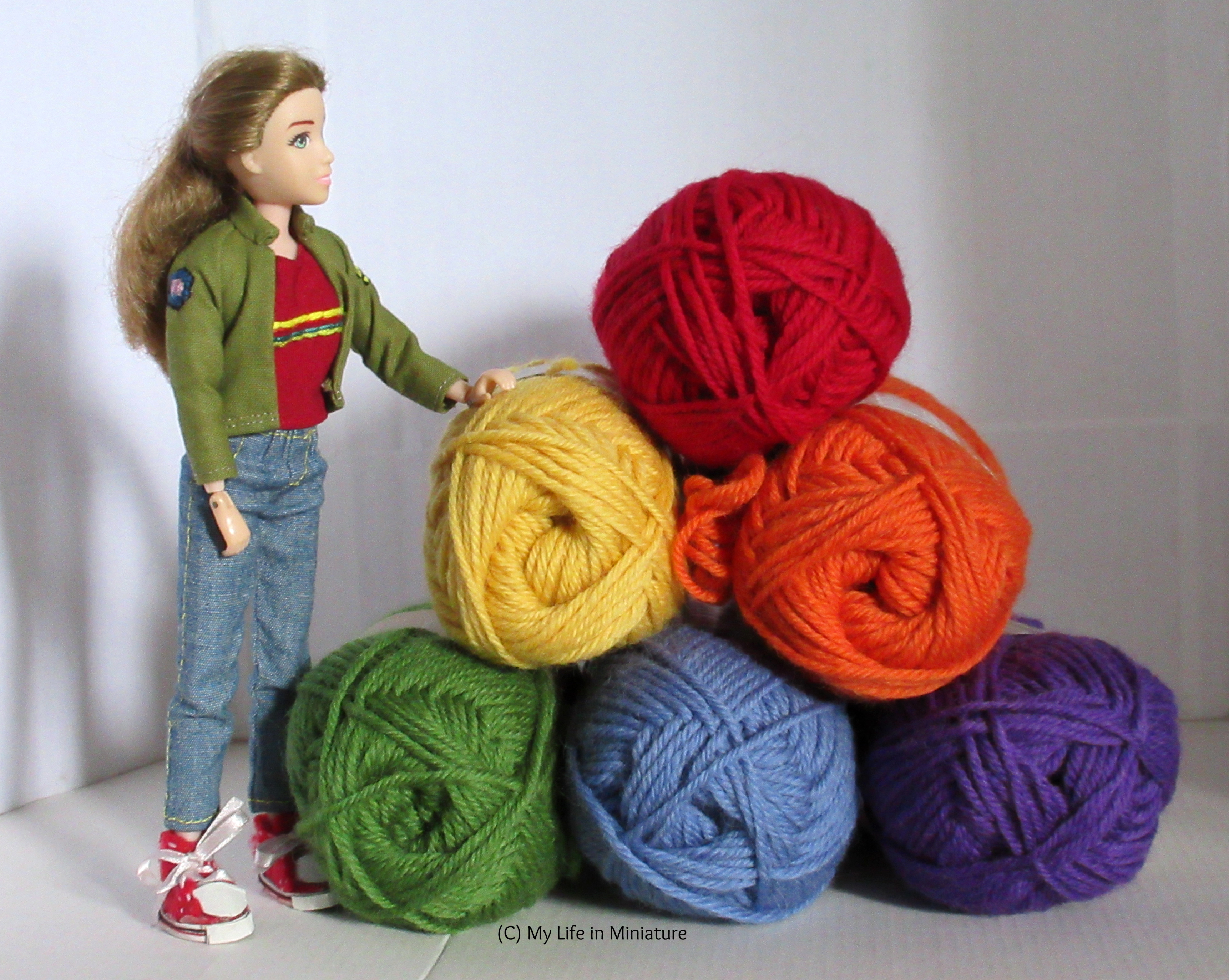 Sarah stands next to a pyramid of stacked balls of yarn. The yarn is in rainbow order from top to bottom. She rests her hand on the closest ball and looks at the top yarn ball.