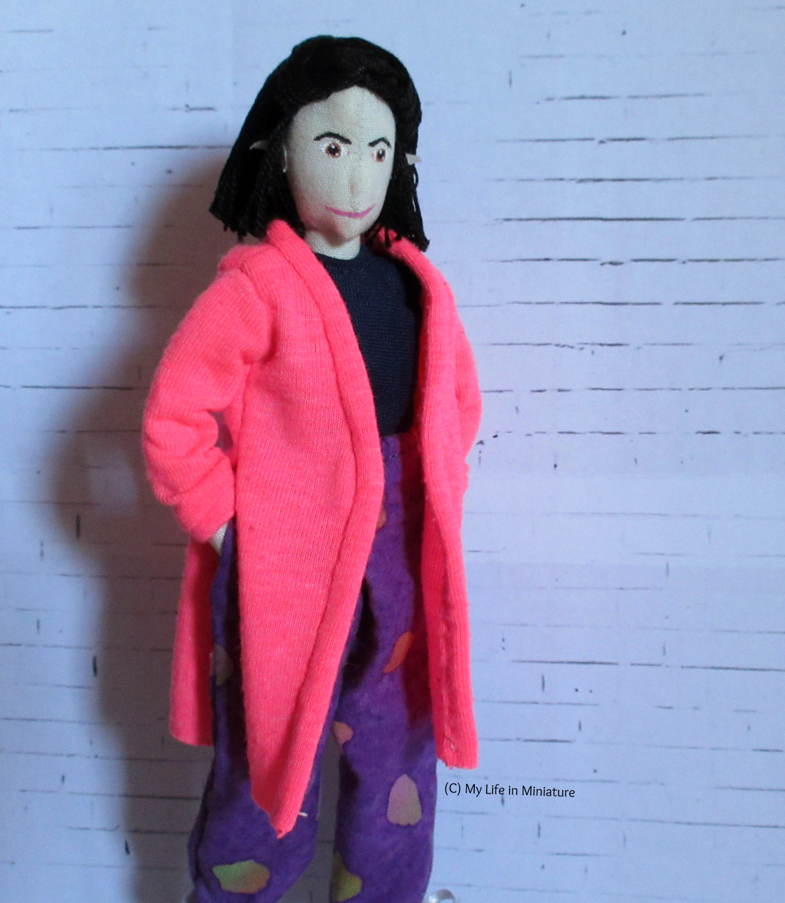 Tiffany wears her neon pink cardigan with her loose purple pants and a navy top. The cardigan goes to her knees, with side seam slits to her waist. Her hands are in her pockets.