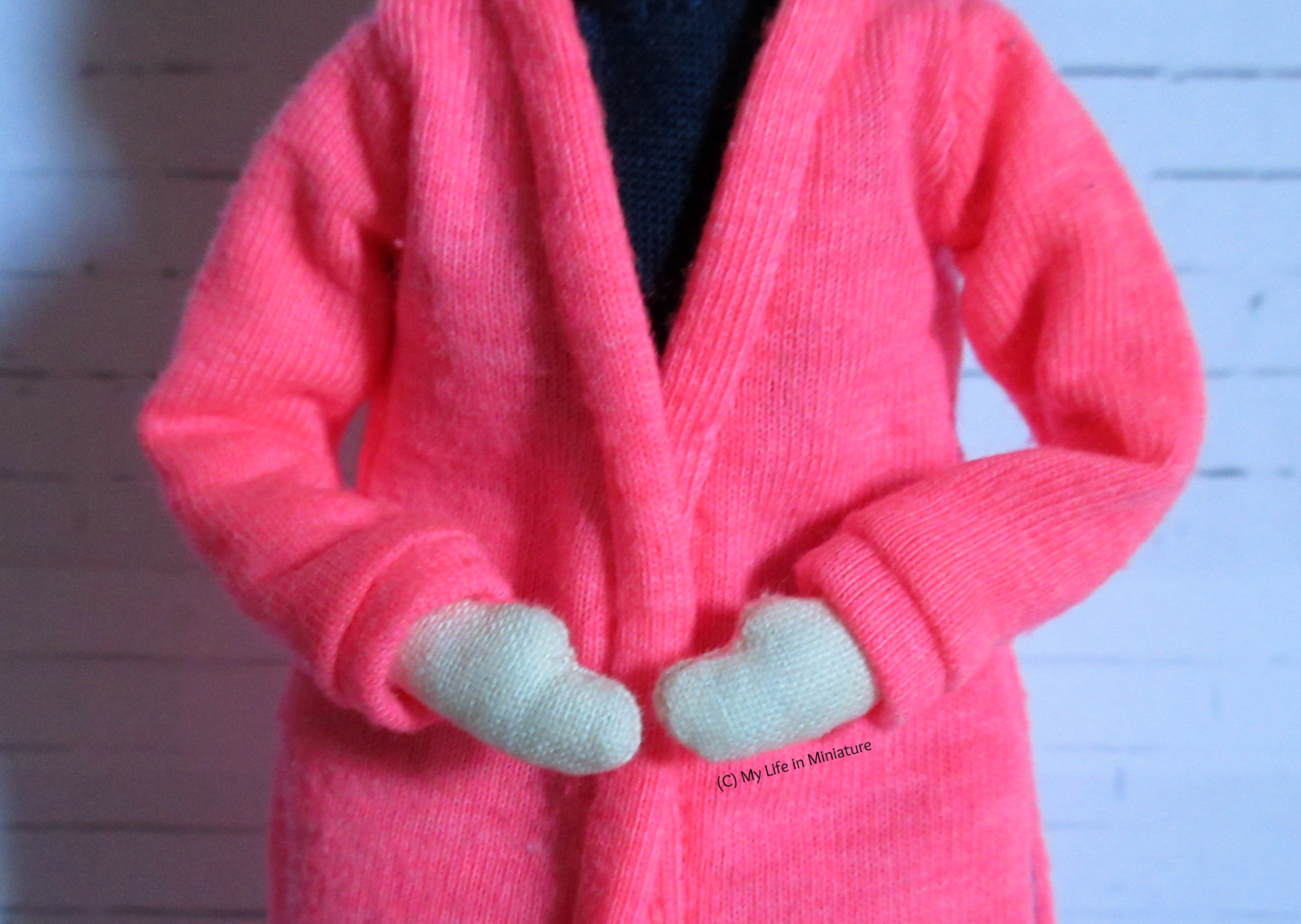 Tiffany wears the neon pink cardigan, her hands held in front of her. The cuffs of her sleeves are visible, as well as the binding around the front opening.