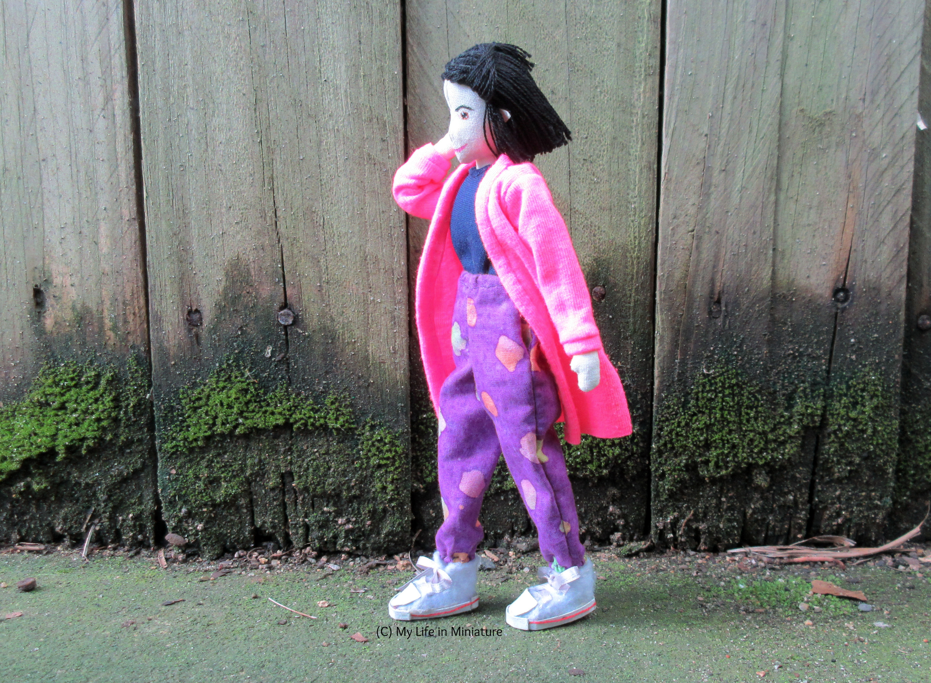 Tiffany walks left-to-right in front of a wood fence. She wears the neon pink cardigan with her loose purple pants and a navy top, ends flowing in the breeze. She tucks some loose hairs behind her ear.