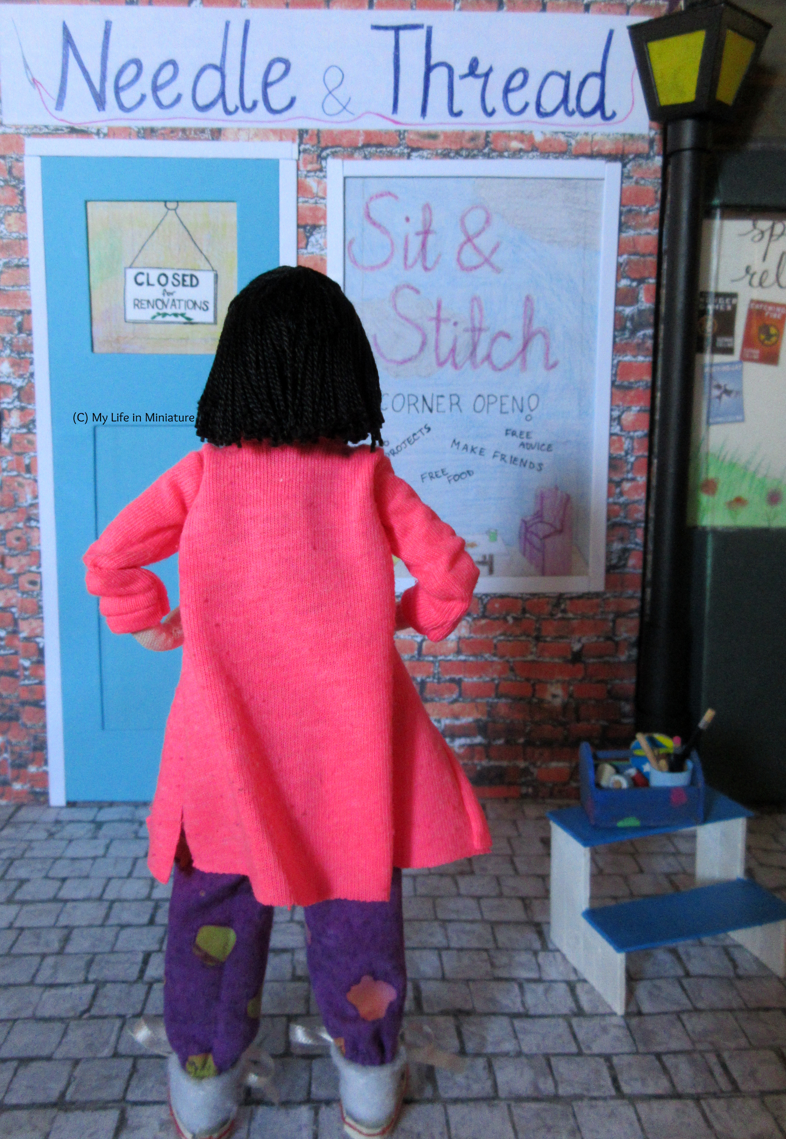 Tiffany stands in front of the front facade of Needle & Thread, back to the camera, hands on hips. A white sign across the top says 'Needle & Thread' in navy, there is a blue door to the left and a window display on the right. The window display says 'Sit & Stitch'.