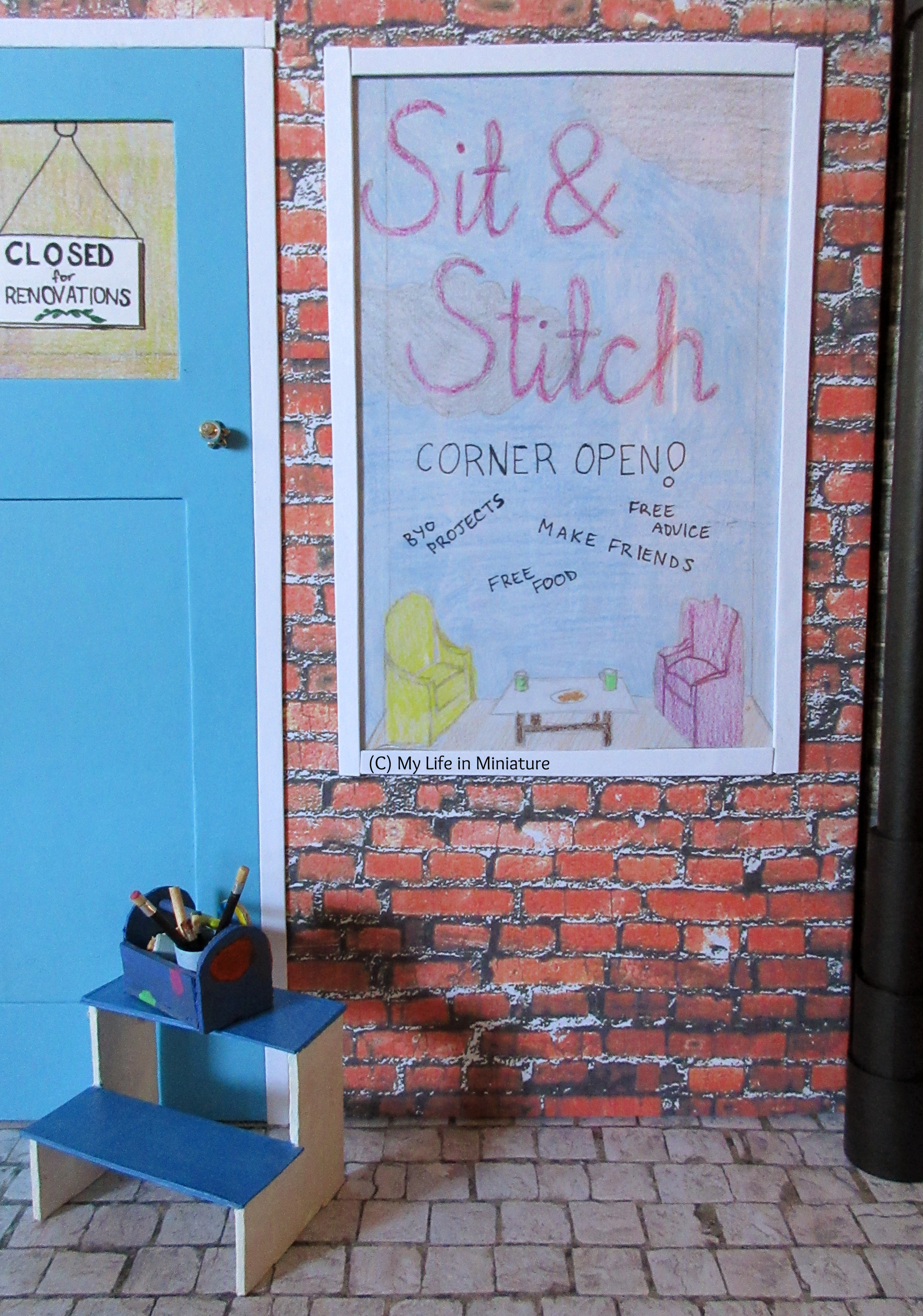 Clear shot of the 'Sit & Stitch' window display. The background to the display is blue sky with some silver clouds; the writing is purple and on the window. At the bottom is a miniature seating area, along with text that says 'Corner Open!' and some of the things offered.