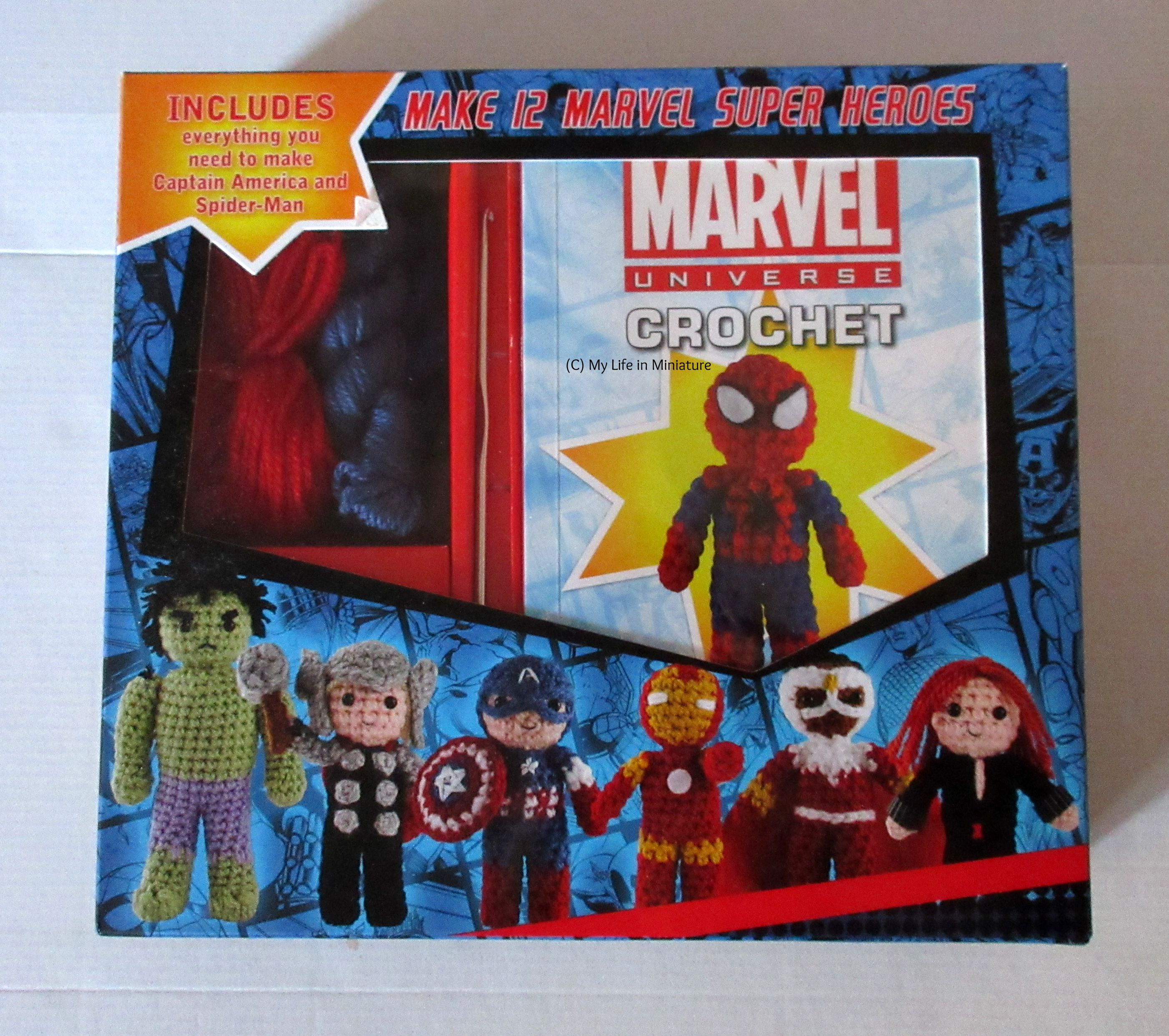A box sits in a white background. The box is printed with, and includes, materials and instructions to make two small Marvel superhero dolls from crochet.