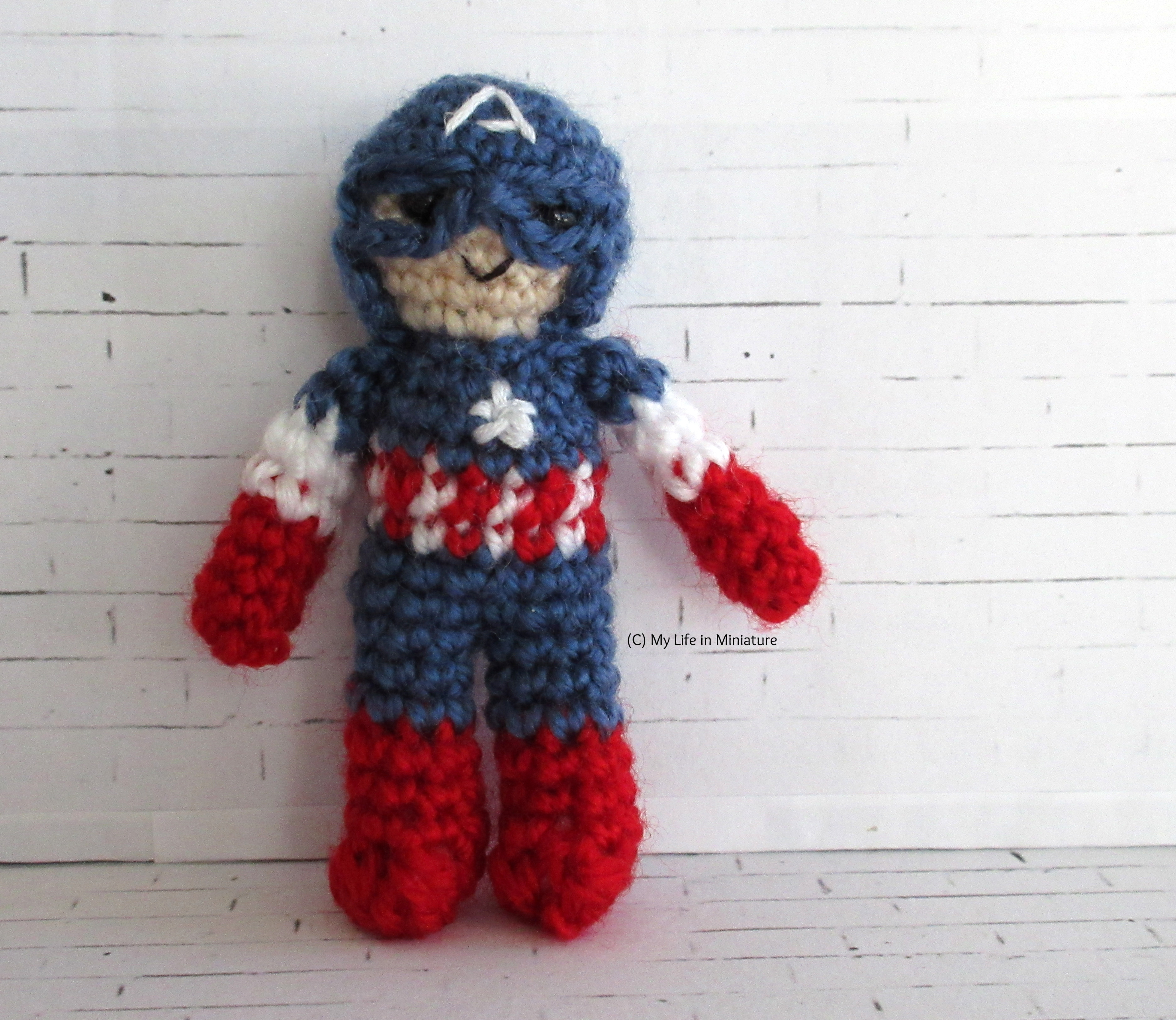 A miniature Captain America crocheted doll stands against a white brick background. He wears the helmet and suit from the first MCU movie, with eye-holes and a red-and-white striped section on the torso.