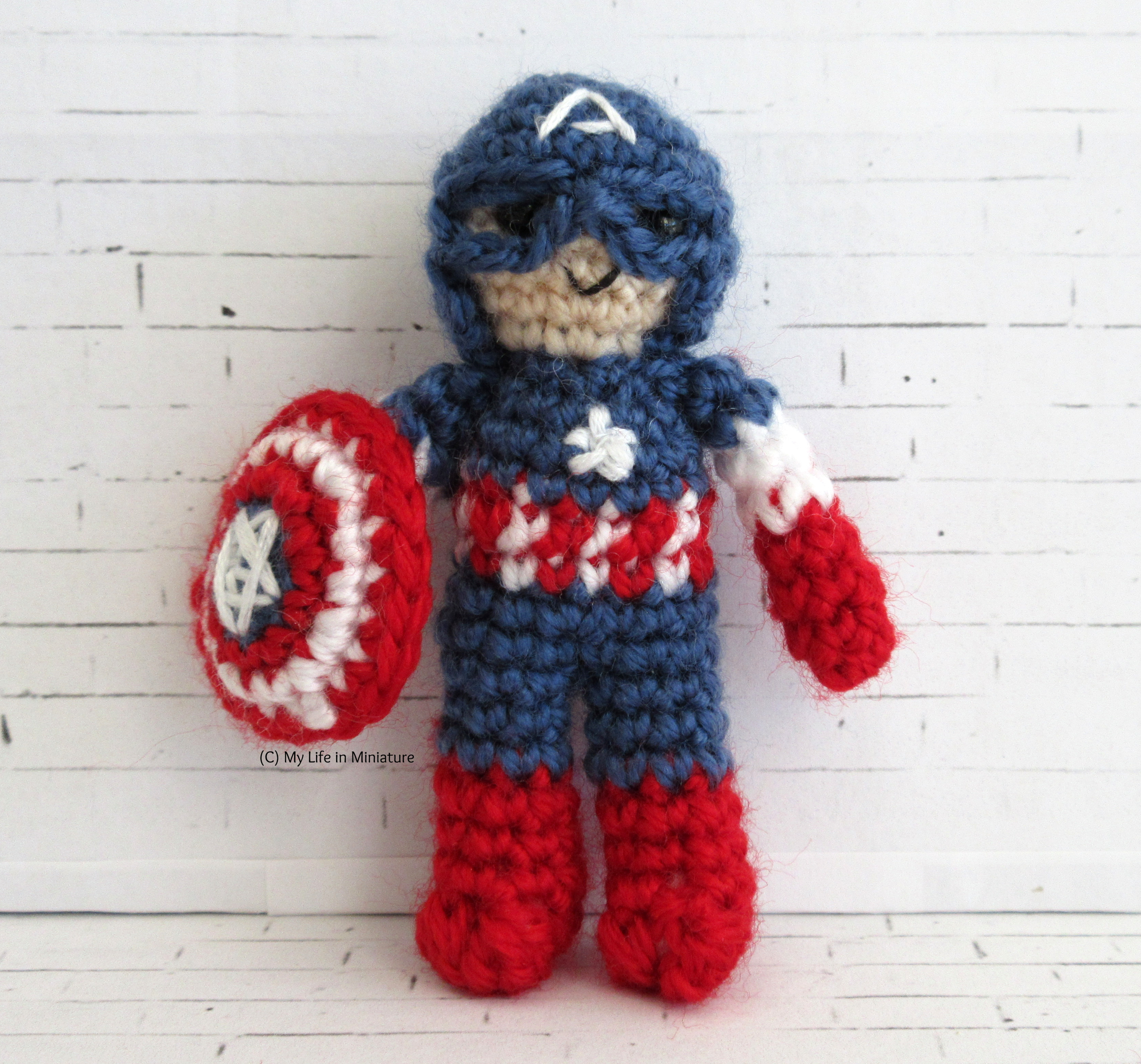 A miniature Captain America crocheted doll stands against a white brick background. He wears the helmet and suit from the first MCU movie, as the last image, and carries the shield in one hand.