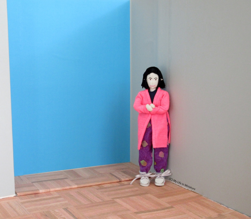 Tiffany is standing facing the camera with her hands clasped in excitement. Behind her is a bright blue wall.