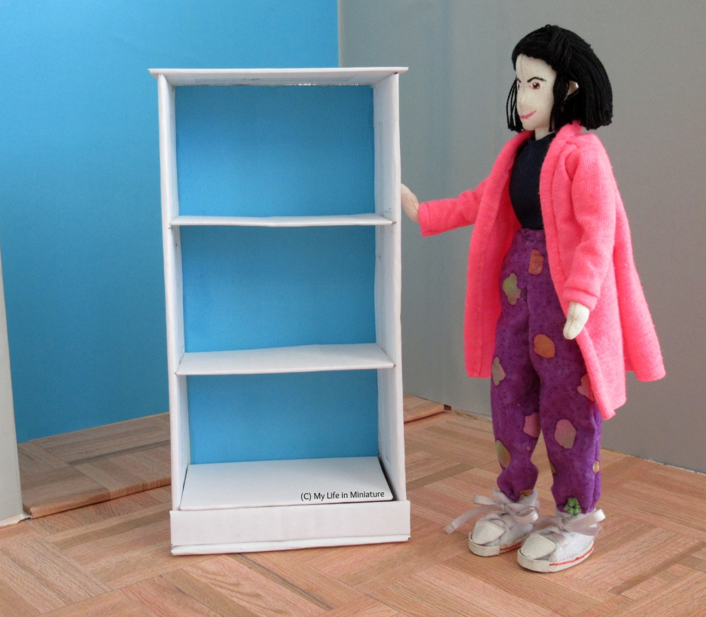 Tiffany stands beside a white bookshelf that is about her height. It has three shelves and is bright blue on its back panel.