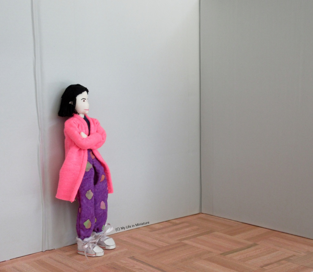 Tiffany stands in a grey-walled corner, arms crossed, deep in thought.