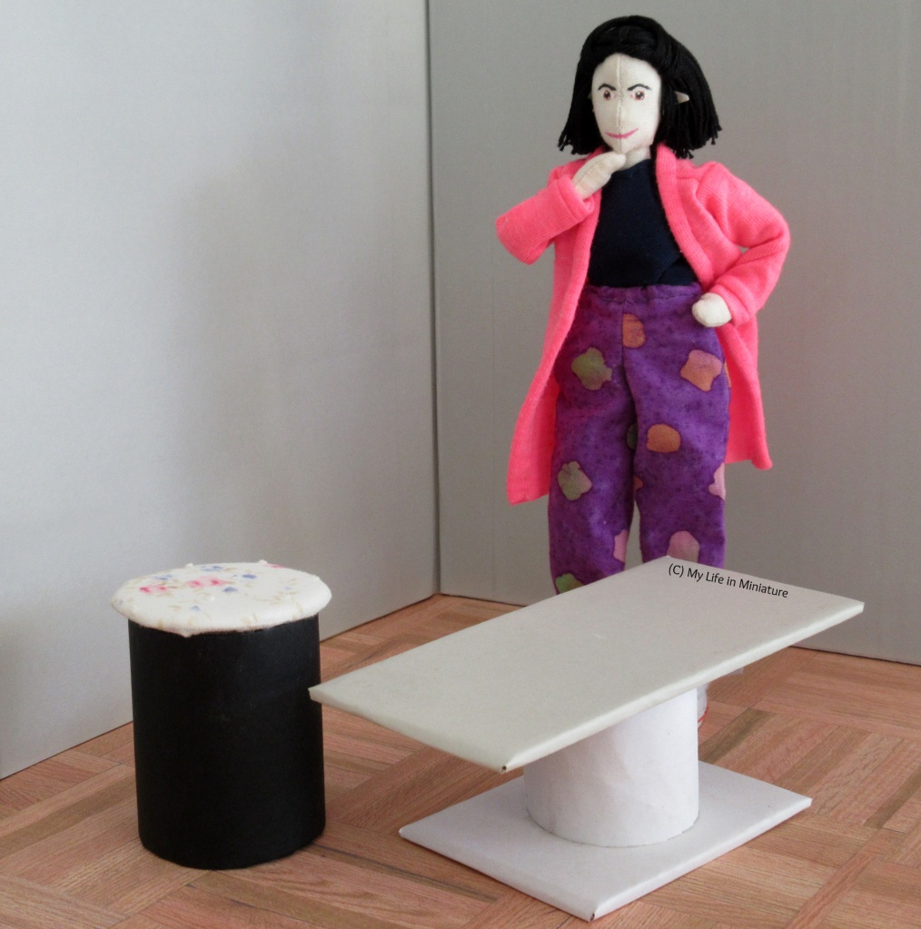 Tiffany stands with hand on hip, chin in hand, thinking. In front of her is a small coffee table (white base and grey top), and a stool (black base, white floral top).