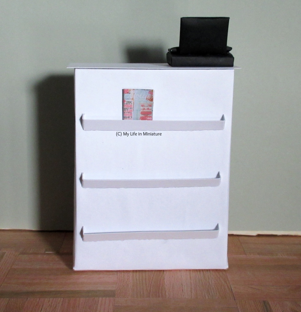 Front view of the Needle & Thread counter. It's white; a black cash register sits on the top right. There are three magazine shelves down the front; the top one has a craft magazine in.