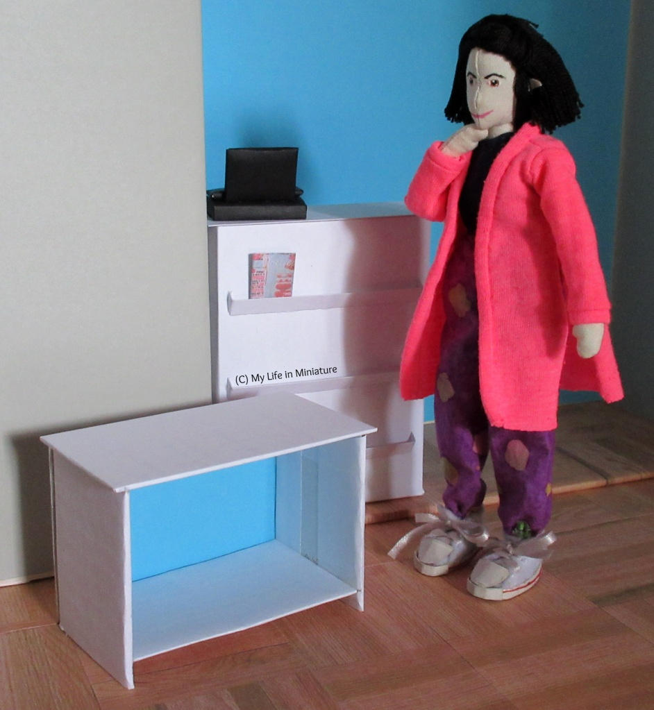 Tiffany stands in front of the counter, hand under chin, thinking. The top and first shelf of the bookshelf sits on the floor in front of Tiffany, who is looking at it.