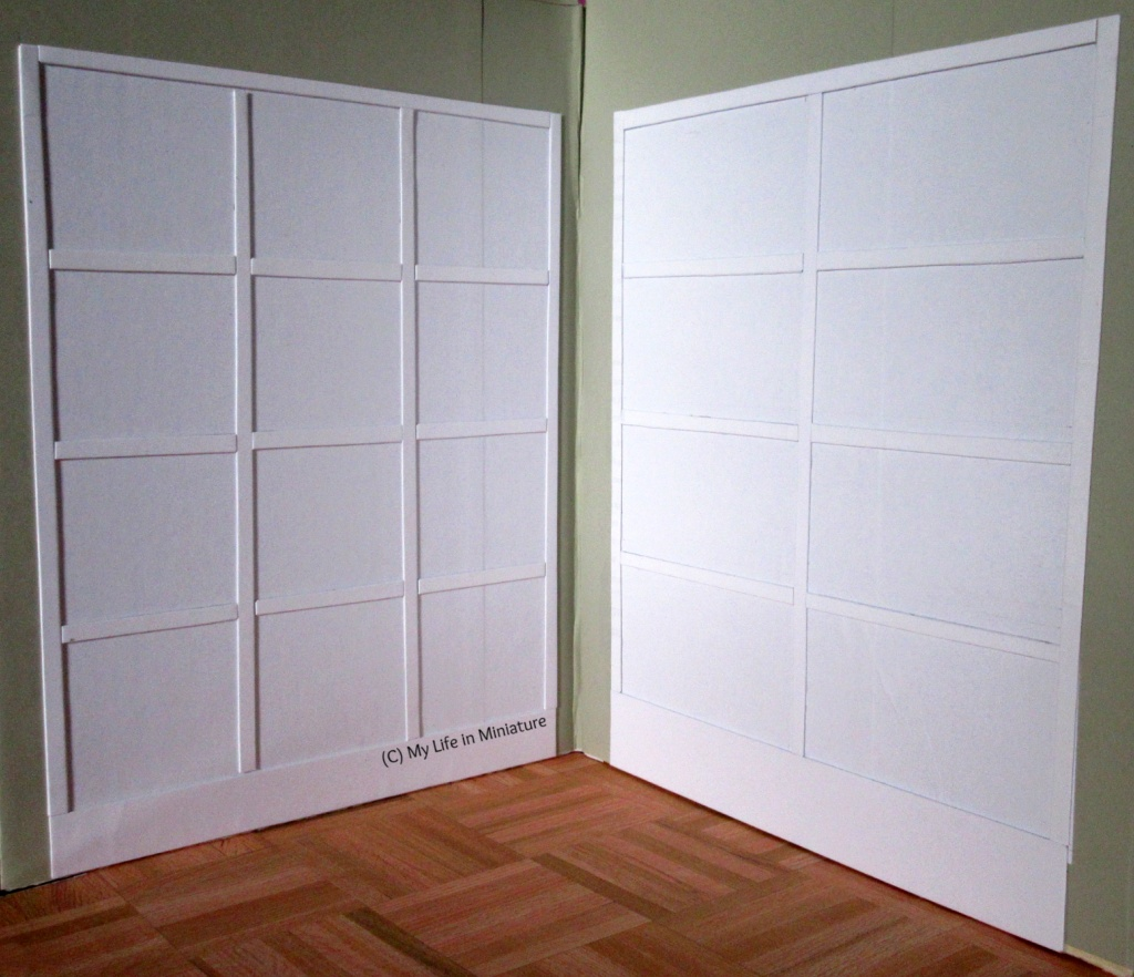 Interior of Needle & Thread. Camera looks into the corner, and on the two walls are two white 'cabinets', that are flat on the walls.
