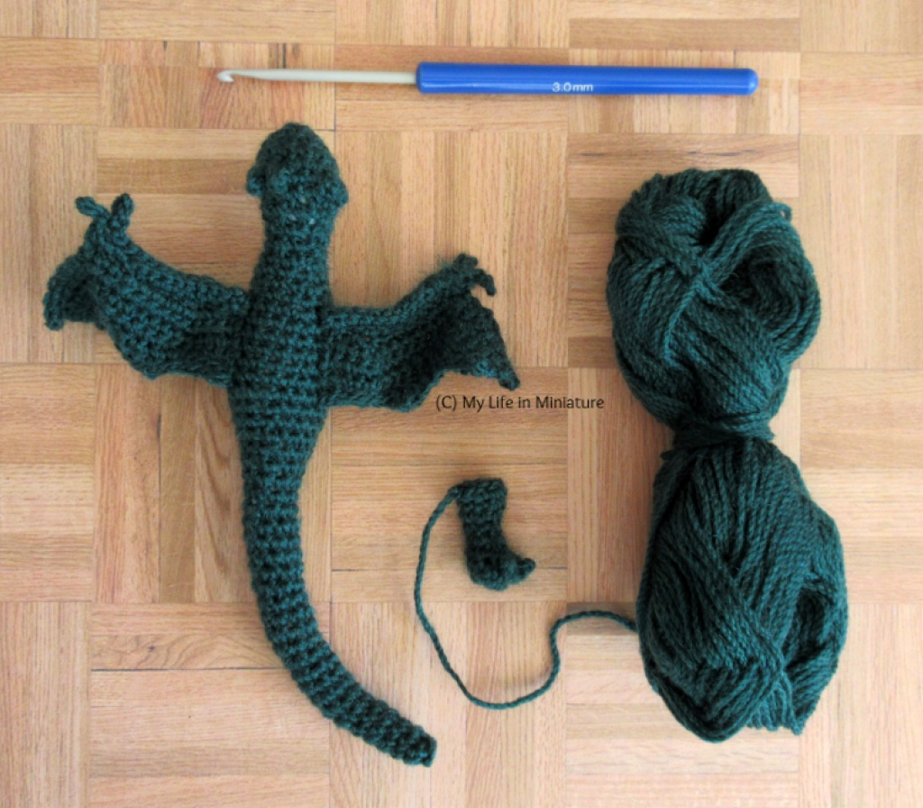 Flatlay of a 3mm crochet hook, a ball of dark green yarn, a dark green crocheted dragon shape without legs, and a small dark green crocheted foot with claws.