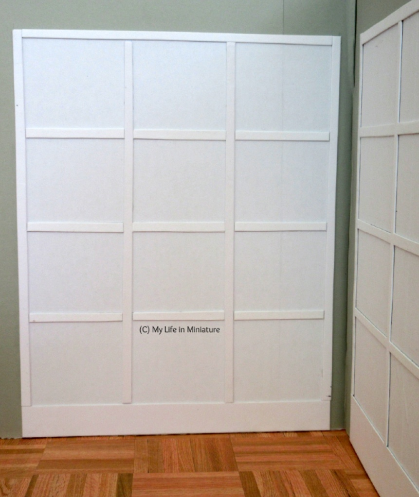 Image shows the left-hand cabinet from the first image. It is white and has twelve square shelves.