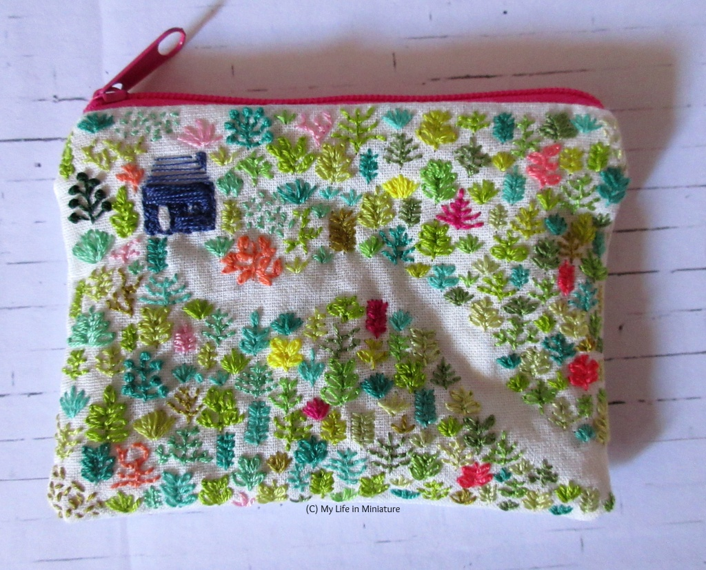 Flatlay view of a white cotton zippered pouch, embroidered with a navy blue house in a green forest. A path through the forest is created with negative space. The zip is bright pink.