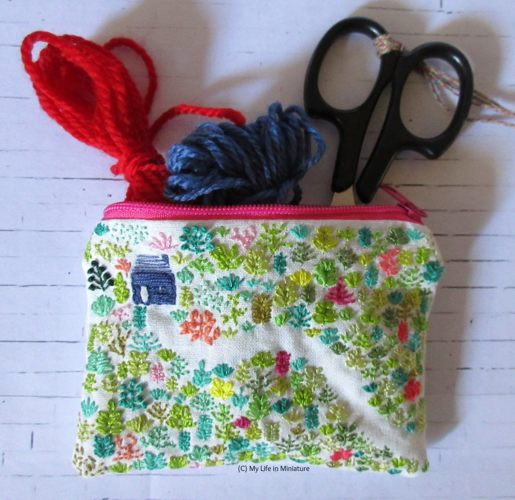 Flatlay view of the zippered pouch, forested side up. Spilling out of it is a pair of black embroidery scissors, and two small skeins of yarn: one red, one blue.
