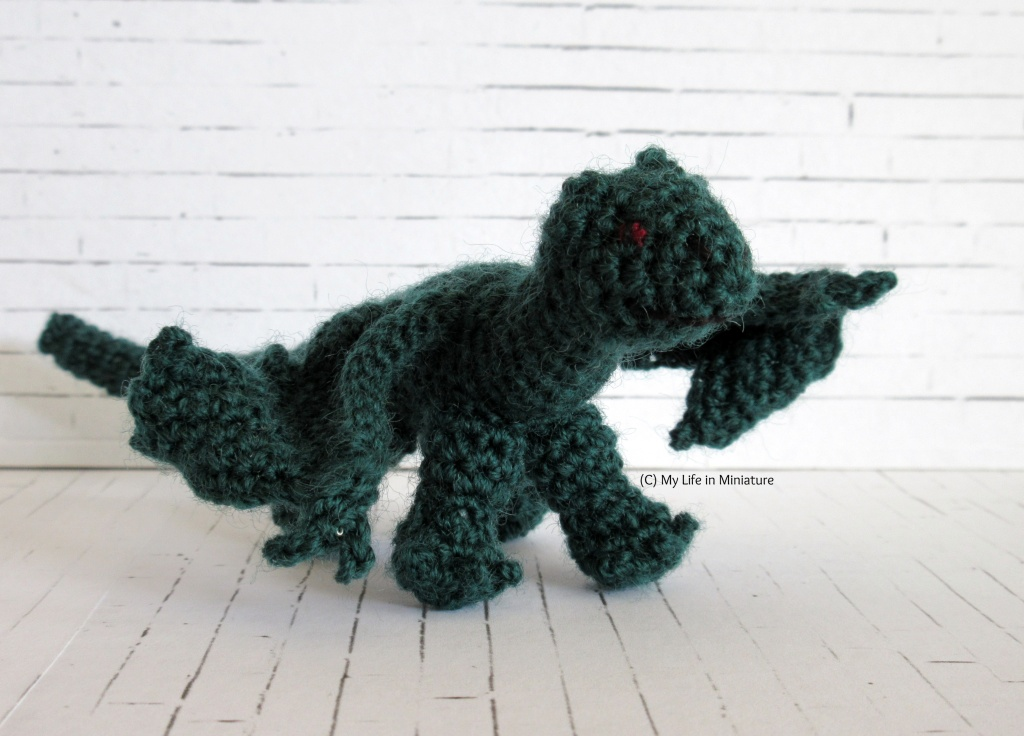 A dark green crocheted dragon stands in front of a white background.
