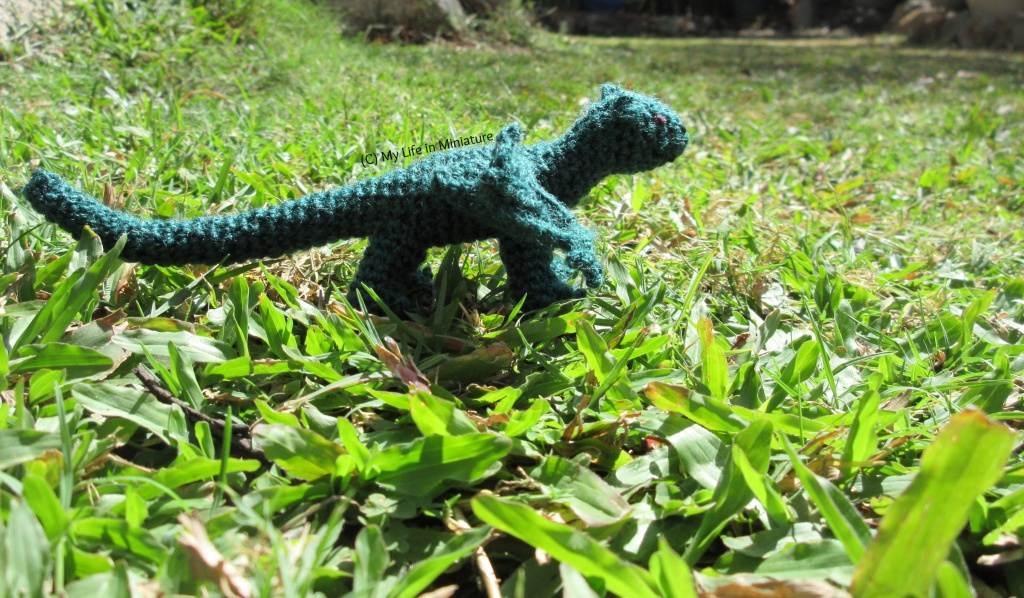 The dragon stands outside, under sunlight on grass.