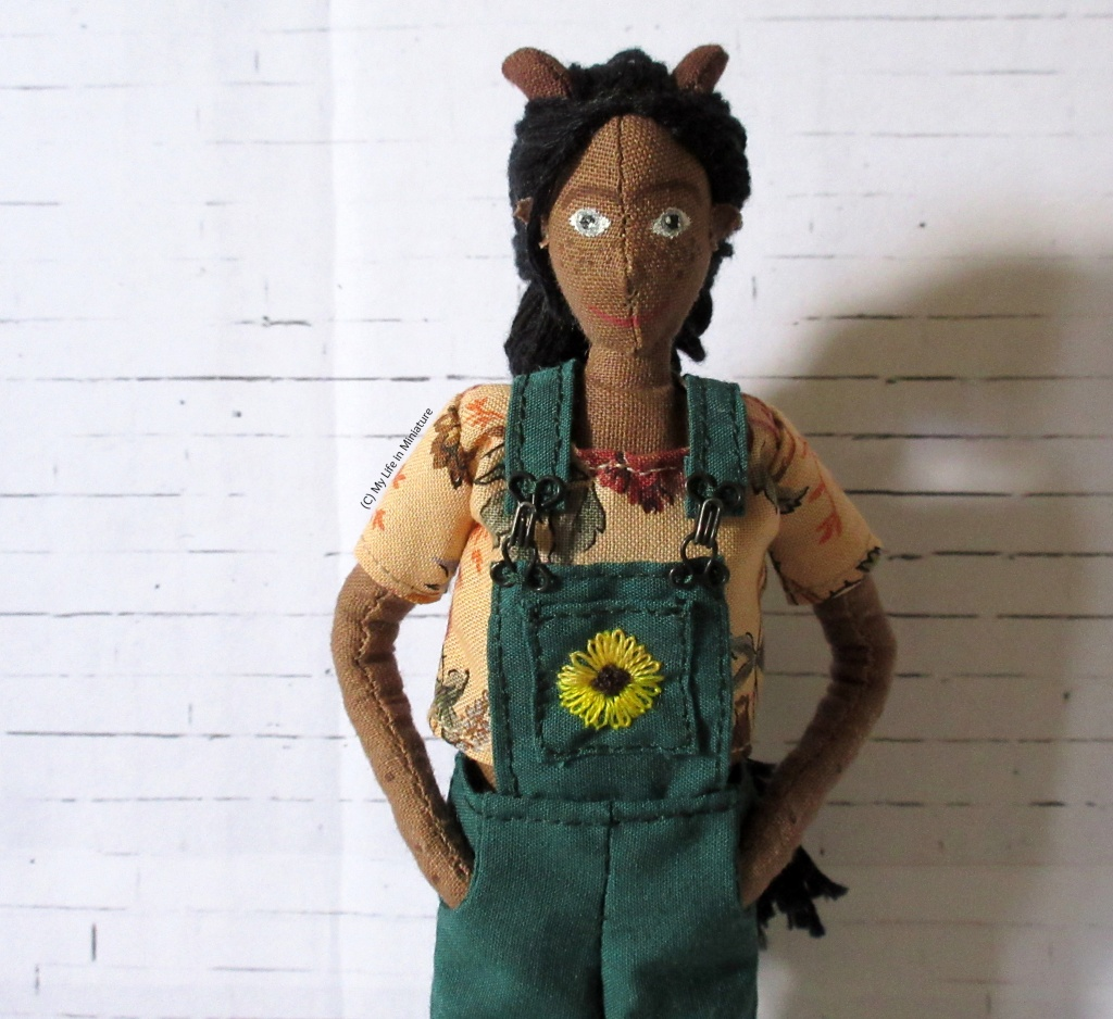 Petra wears the top under her green overalls against a white brick background.